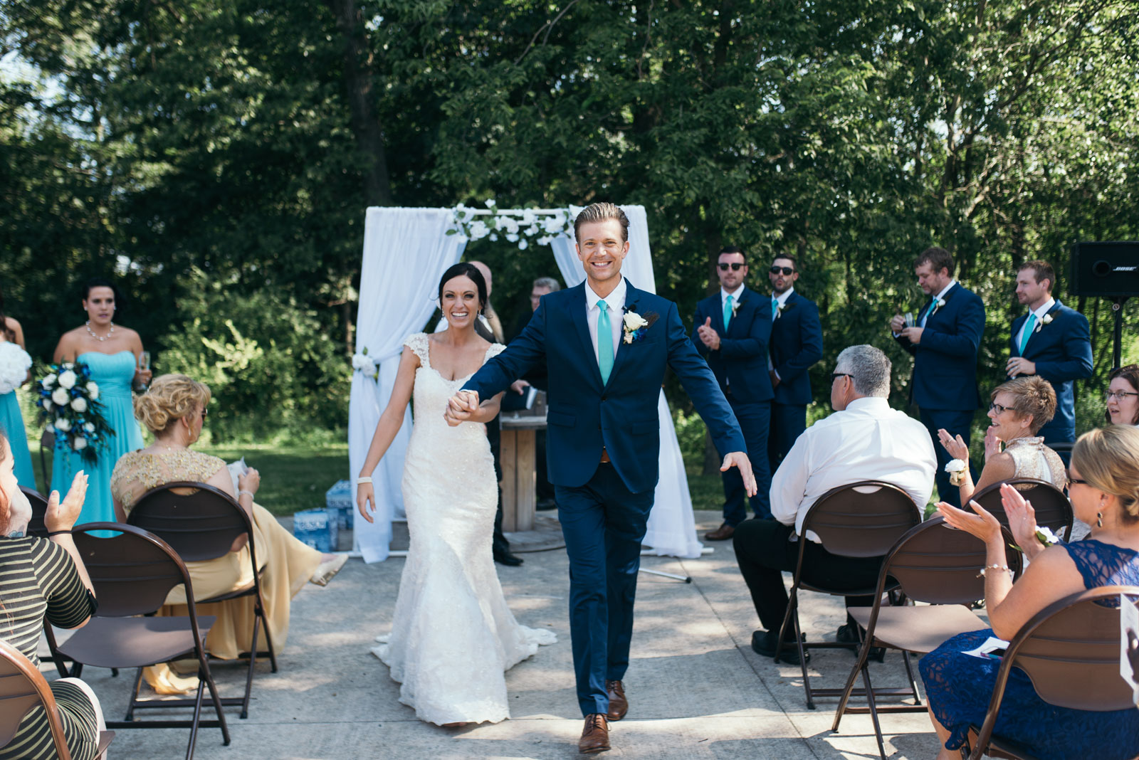 bride and groom walk down aisle after wedding ceremony at squaw creek park