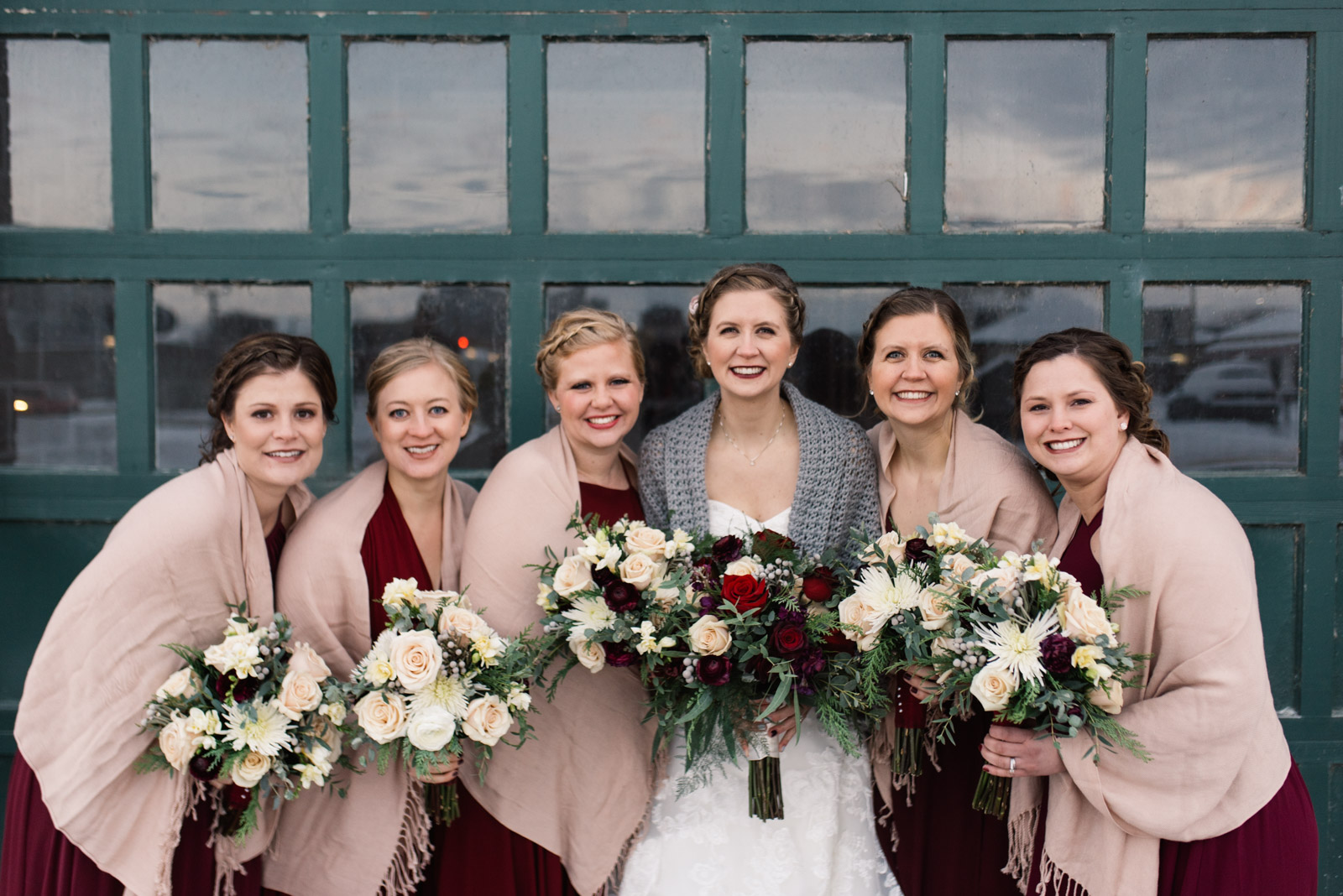 bride and bridesmaids holding flowers in front of green door cedar rapids newbo wedding