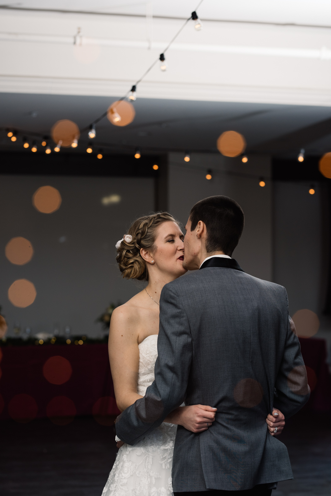bride and groom kissing under string lights eastbank wedding venue