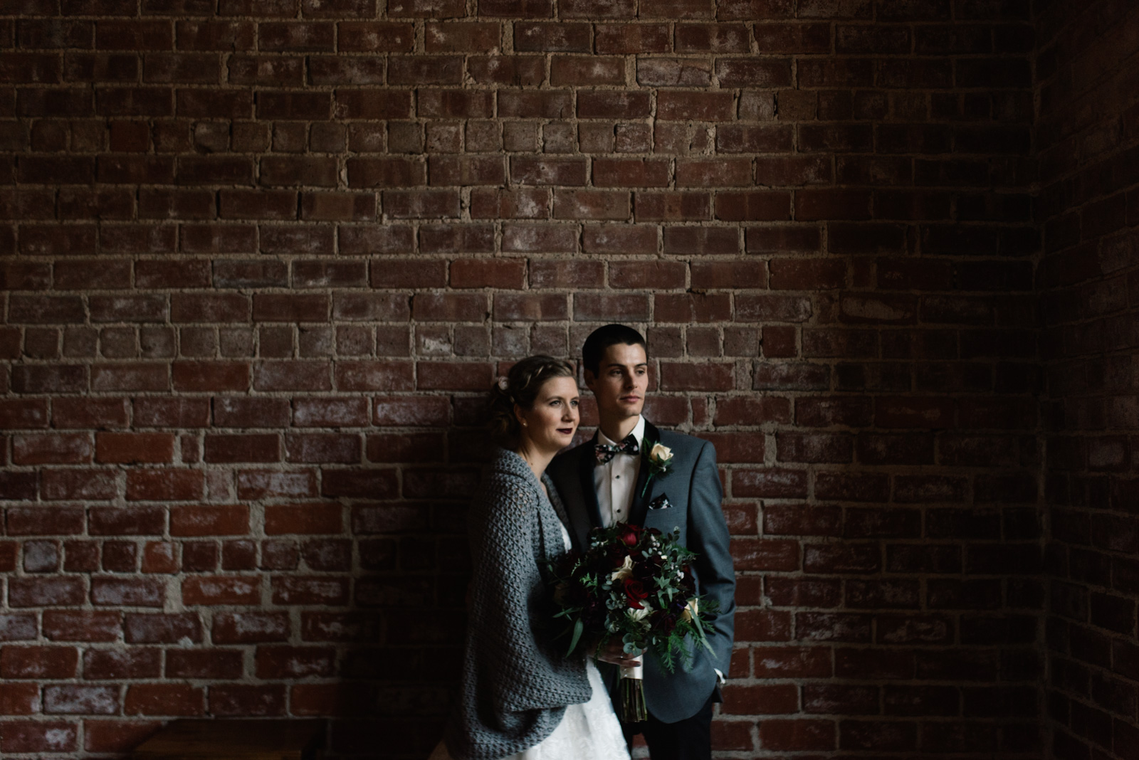 bride and groom next to brick wall black sheep social club winter wedding