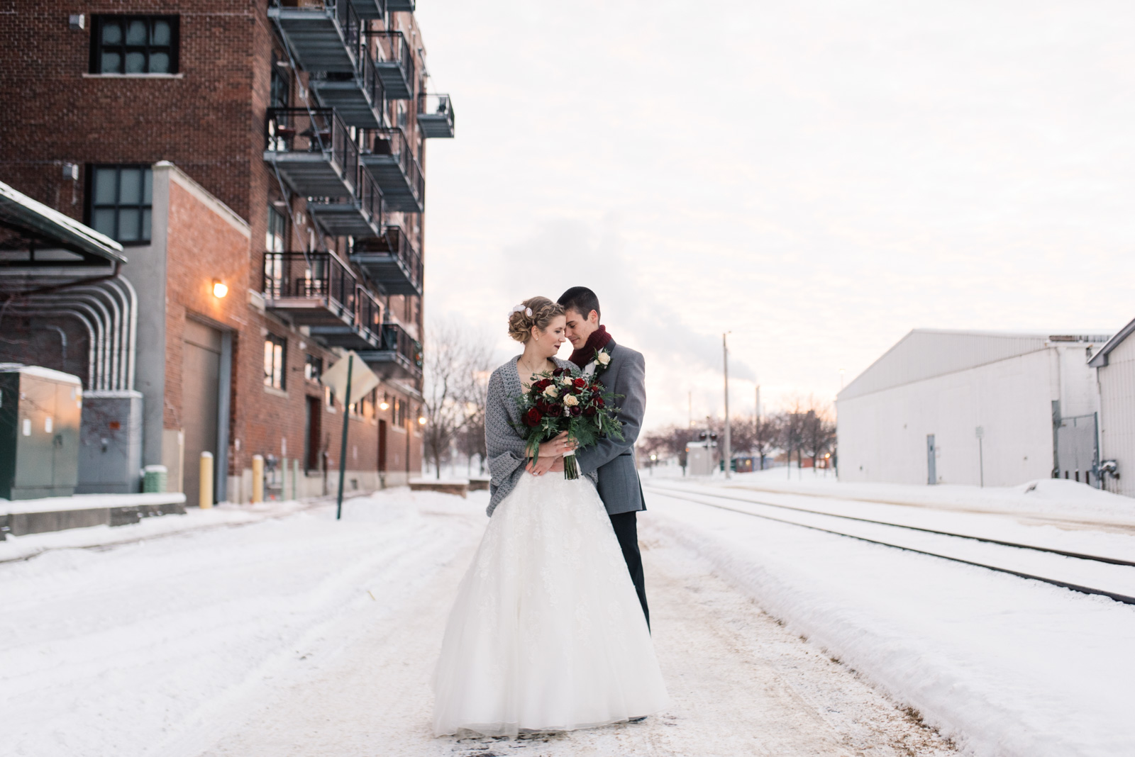 bride and groom standing in snow cedar rapids winter wedding