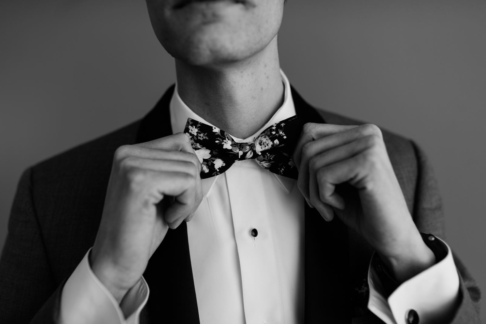 groom adjusting floral bow tie