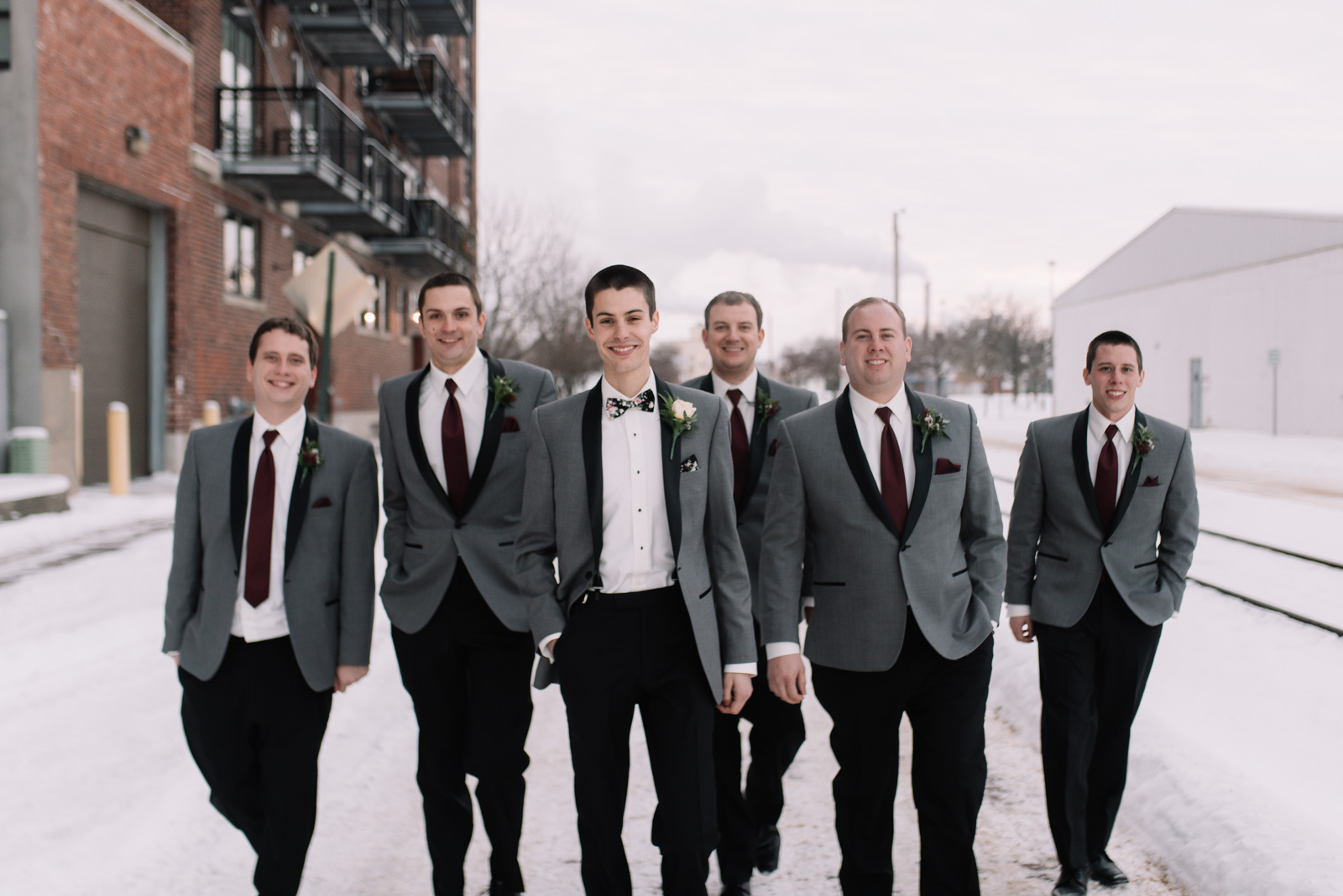groom and groomsmen walking cedar rapids winter wedding