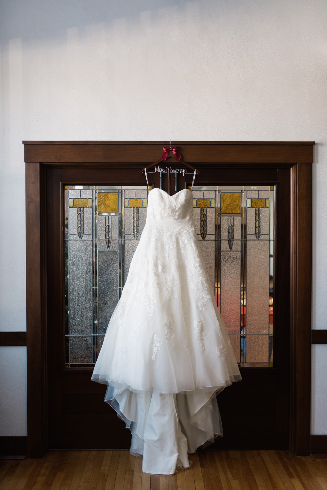 wedding dress hanging on custom wedding hanger in front of stain glass doors