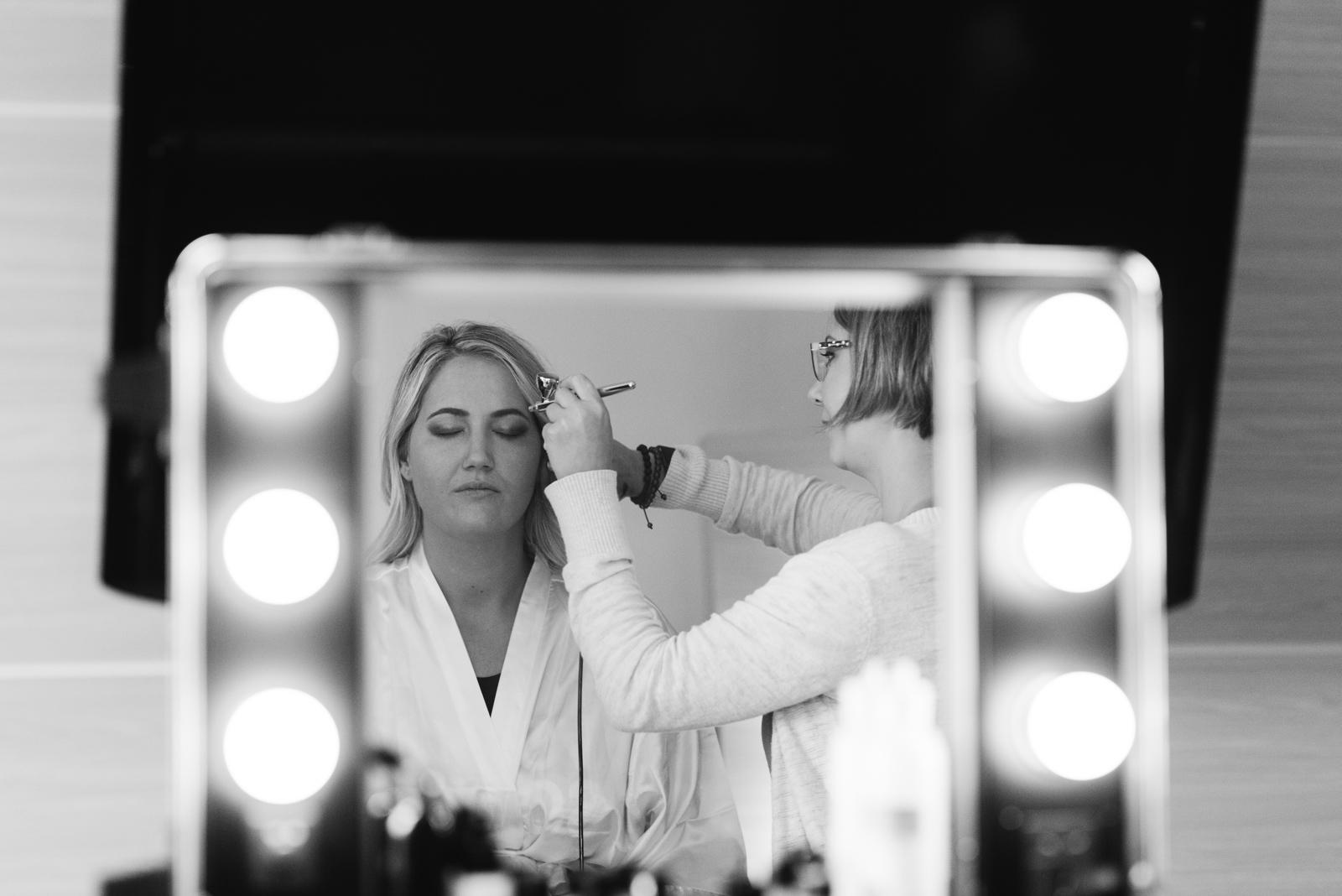 bride getting makeup done in mirror cedar rapids marriott