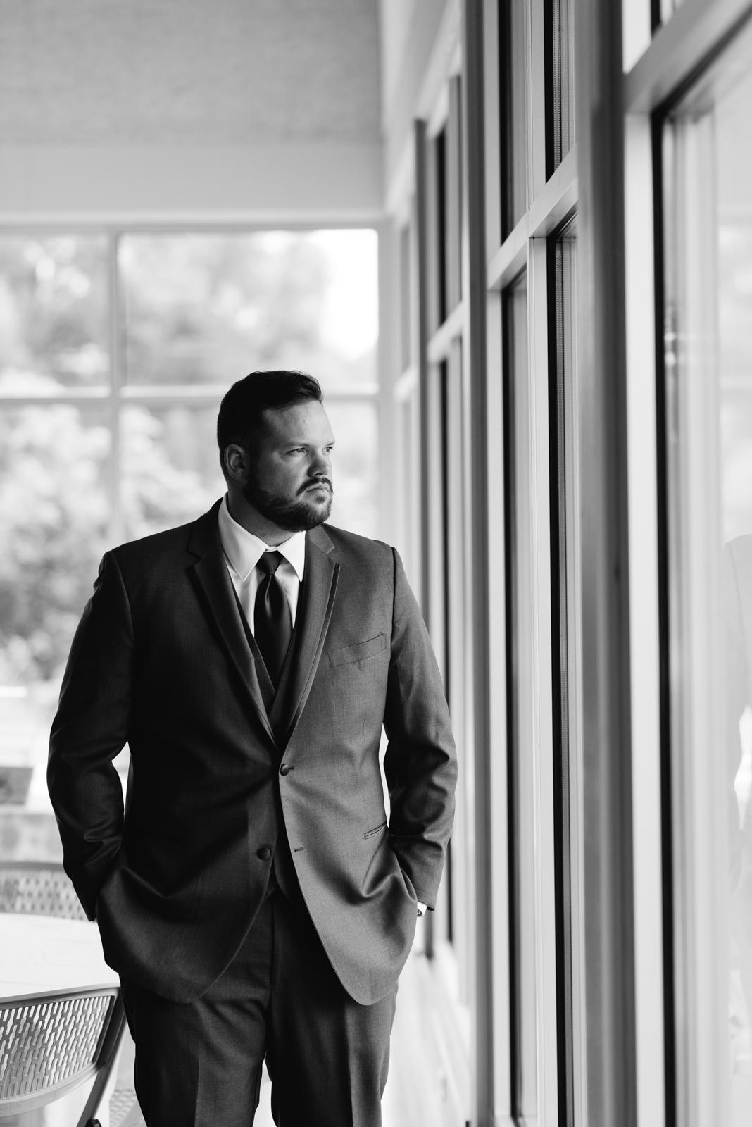 Groom standing in window cedar rapids wedding