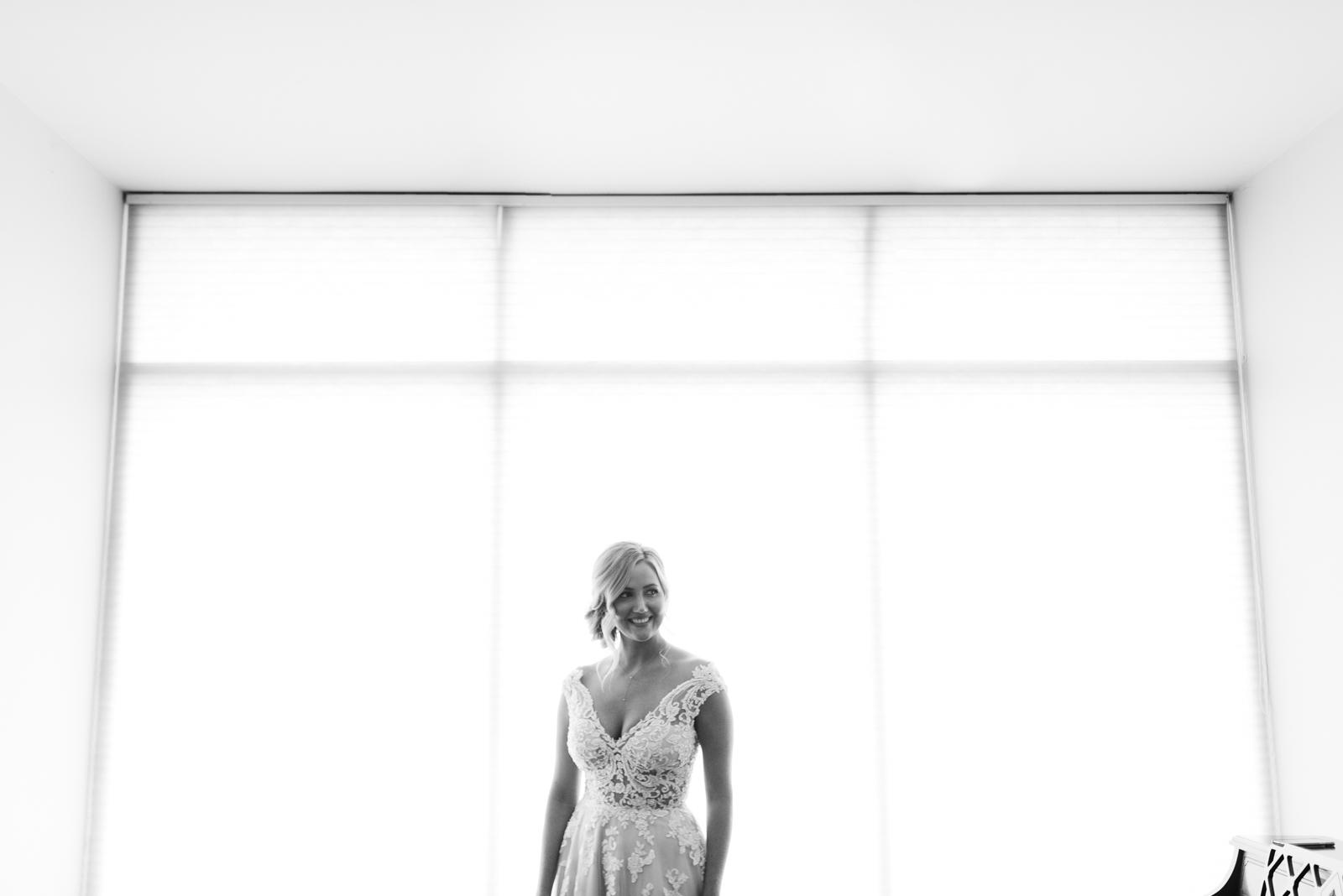 bride in front of large windows St. John XXIII Parish wedding
