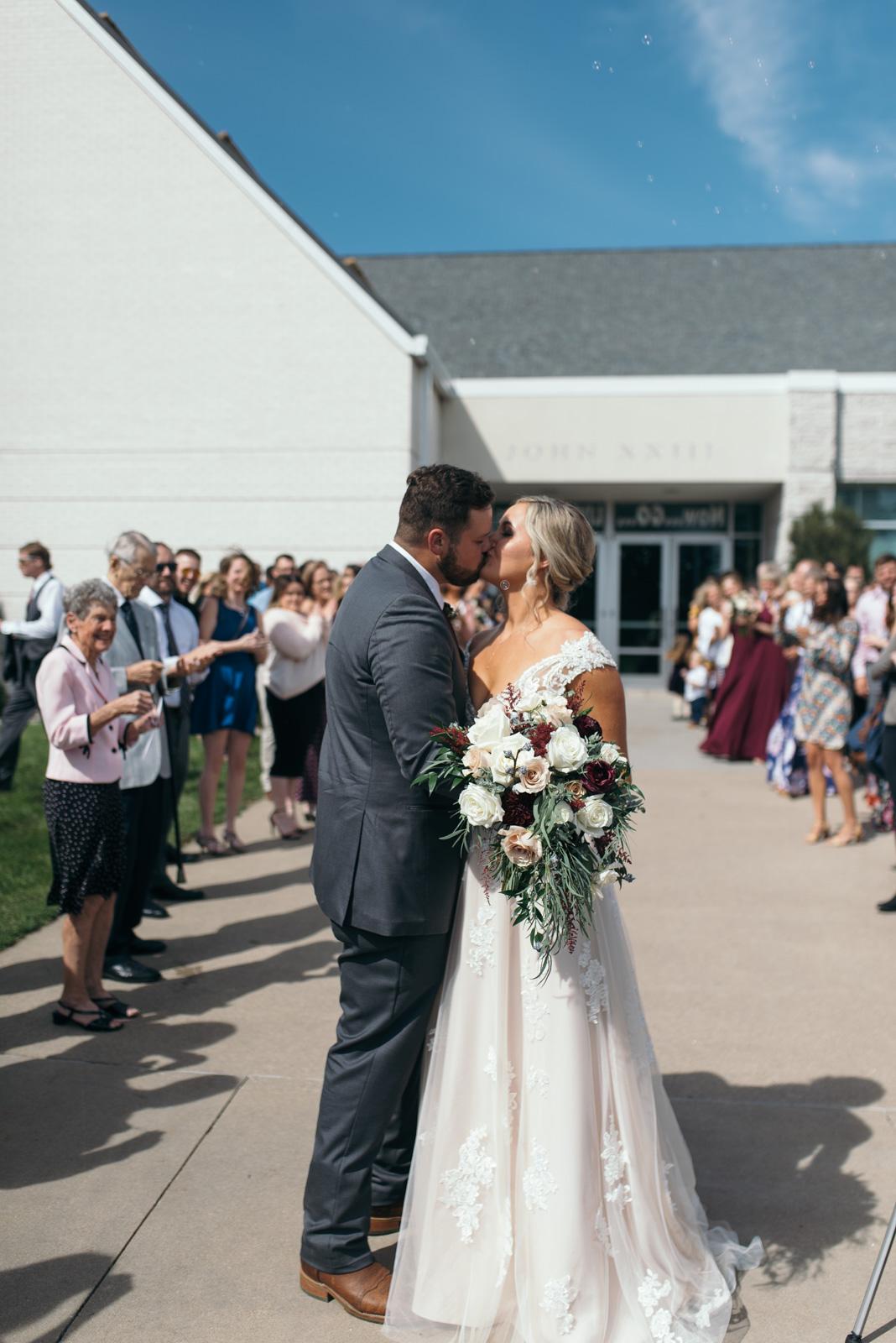 bride and groom kissing outside St. John XXIII Parish wedding