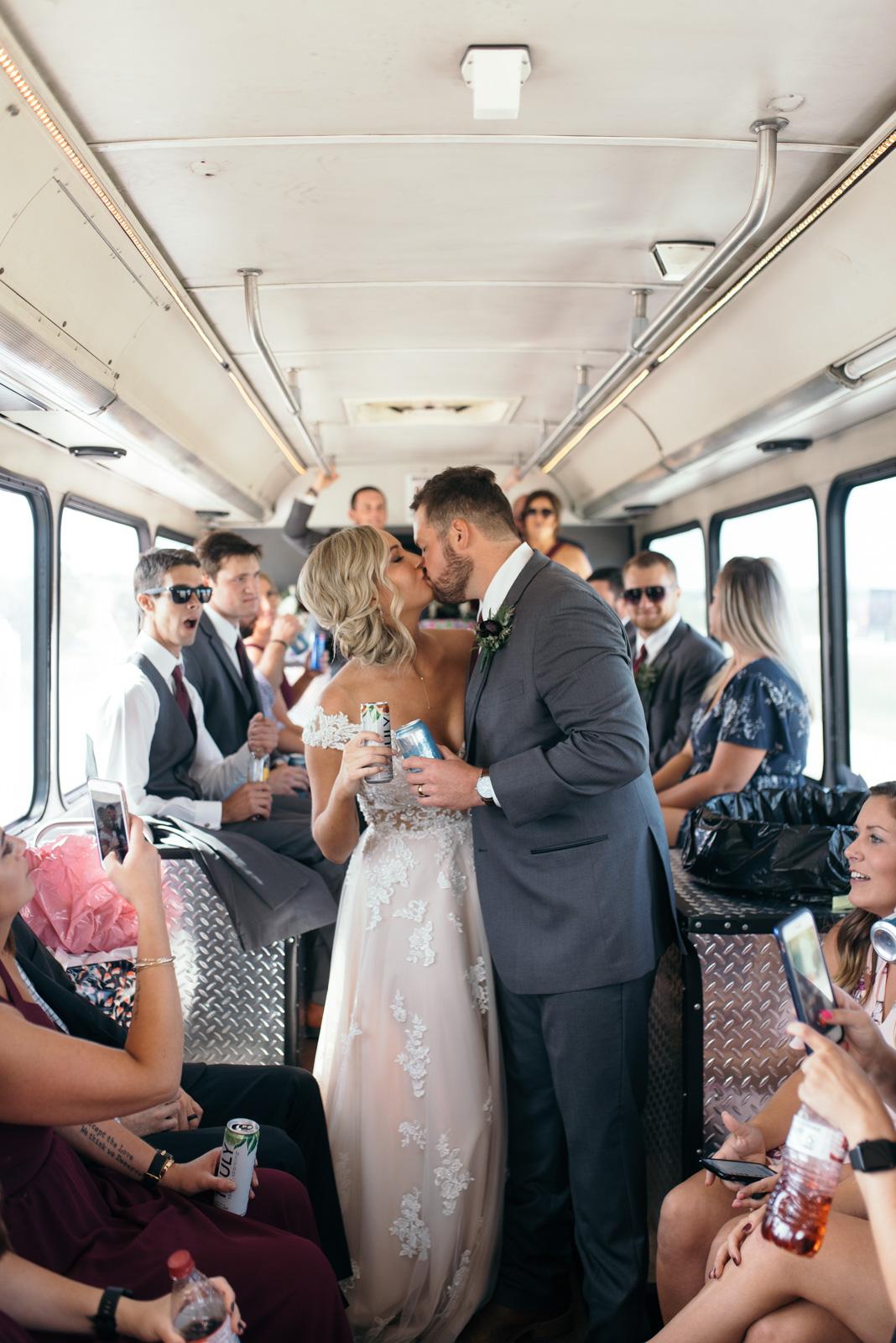 bride and groom kissing on cedar rapids wedding party bus