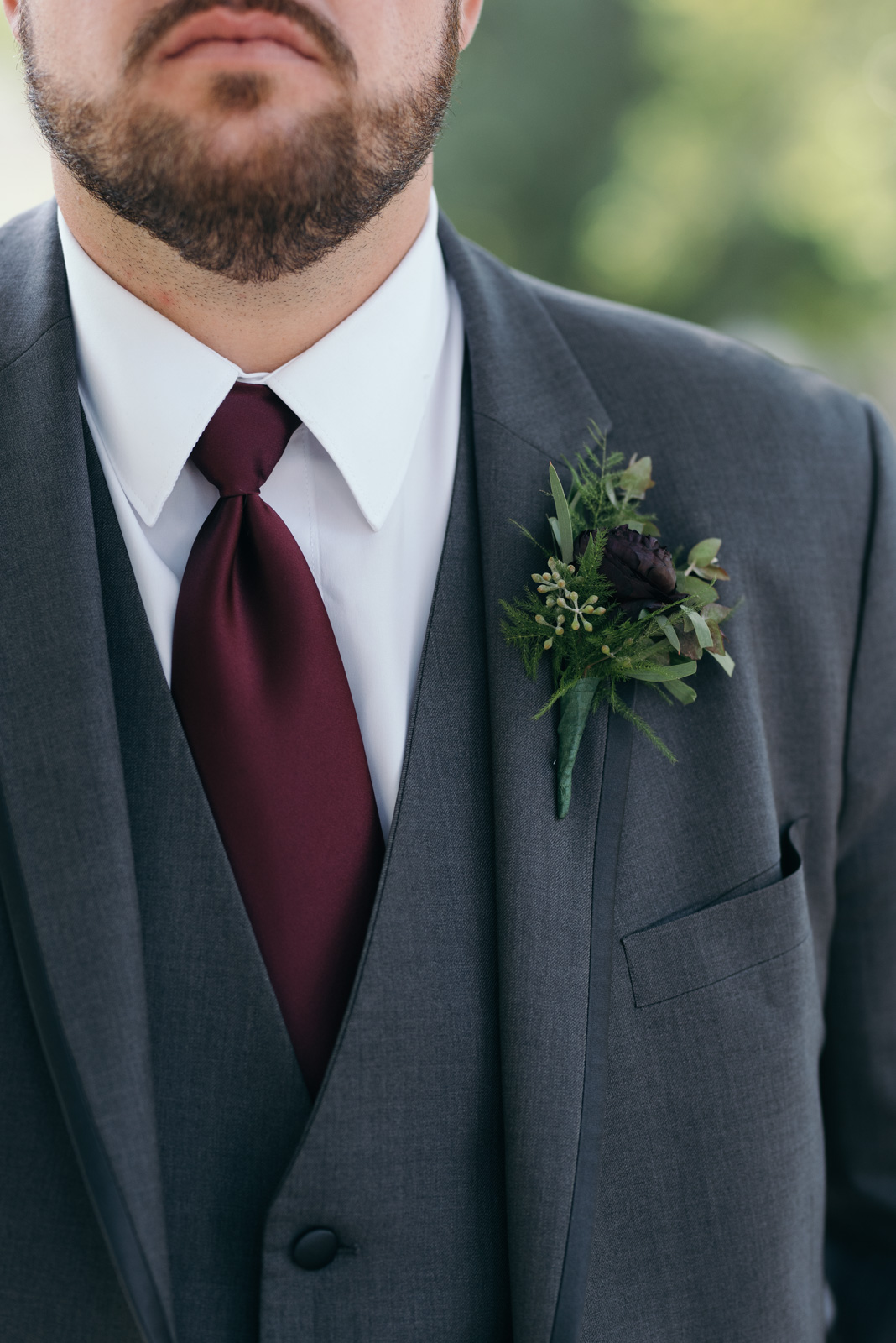 grooms suit with maroon tie and boutonniere