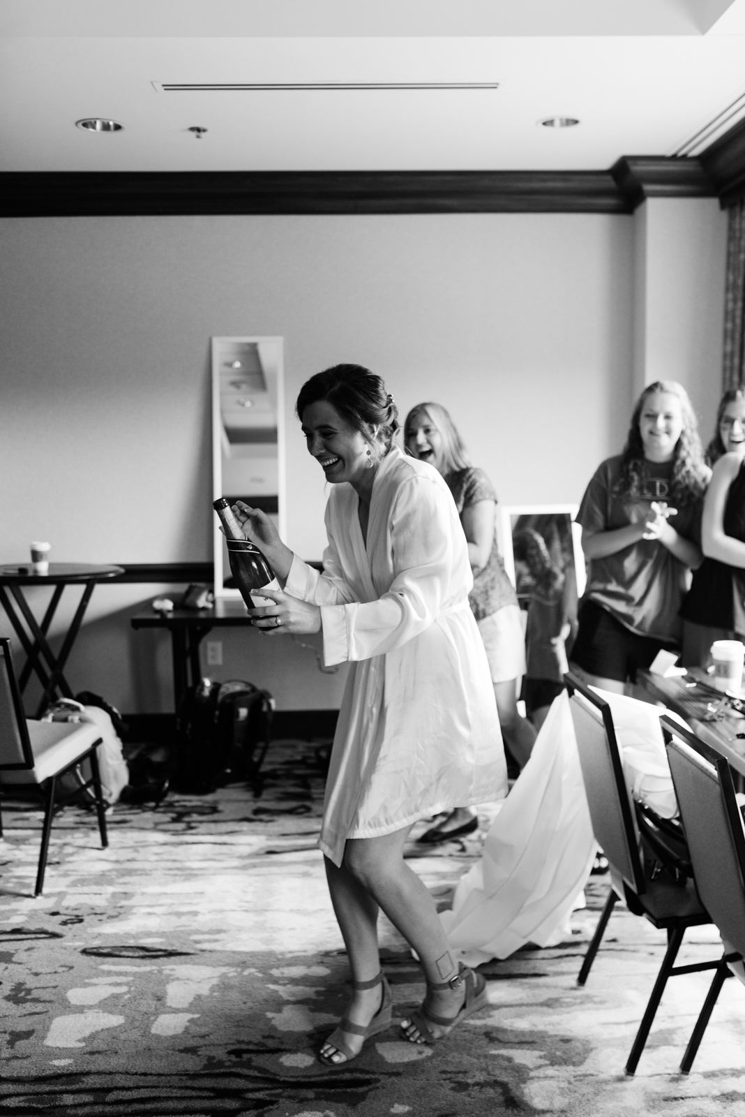 Bride popping champagne at Coralville Marriott Hotel Wedding
