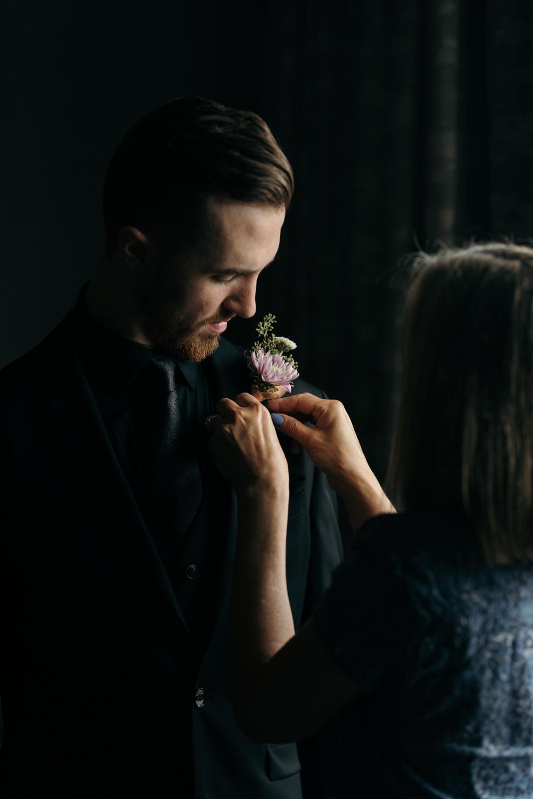 groom getting boutonniere Coralville Marriott Hotel Wedding