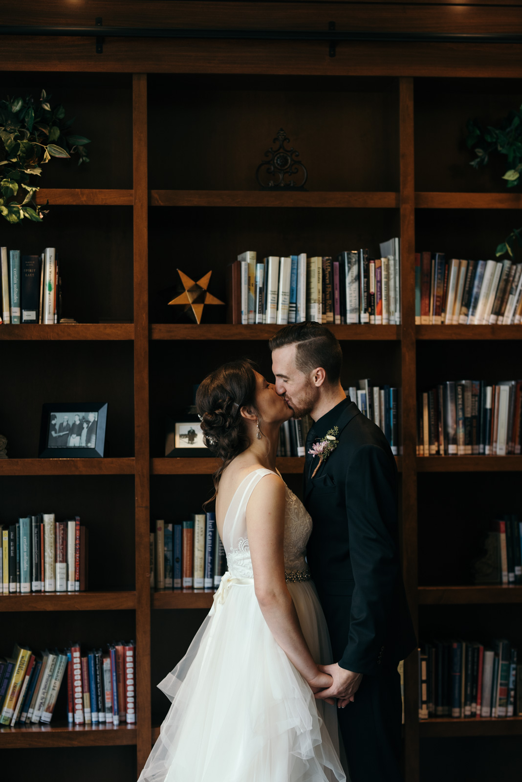 bride and groom kissing in the library Coralville Marriott Hotel Wedding