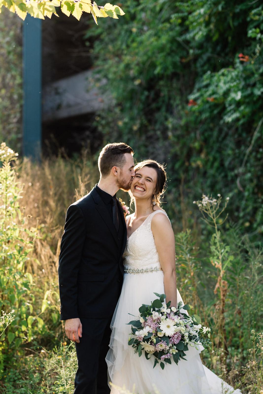 groom kissing brides cheek Coralville Marriott Hotel wedding venue