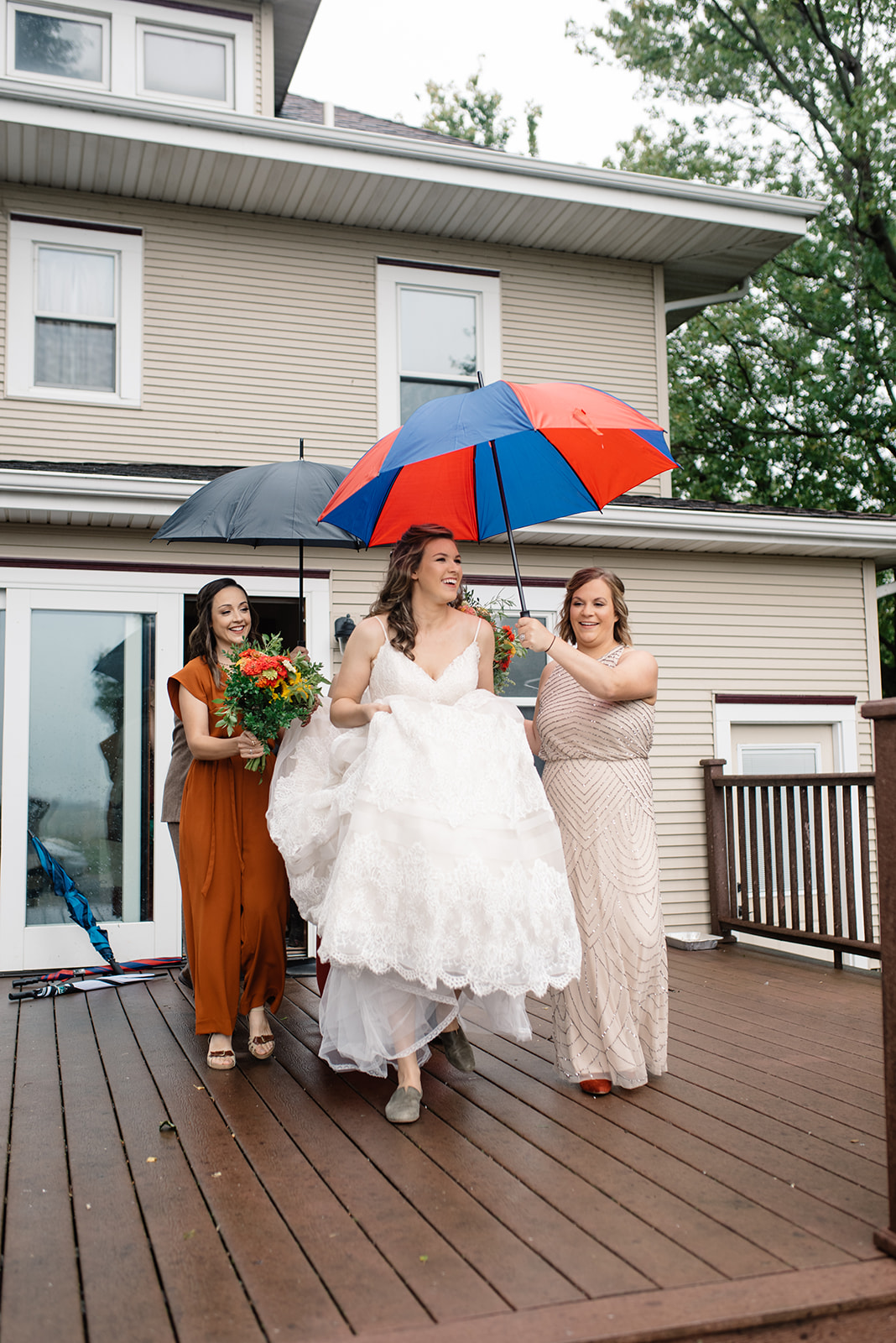 bride and bridesmaids walking outside umbrellas october iowa wedding