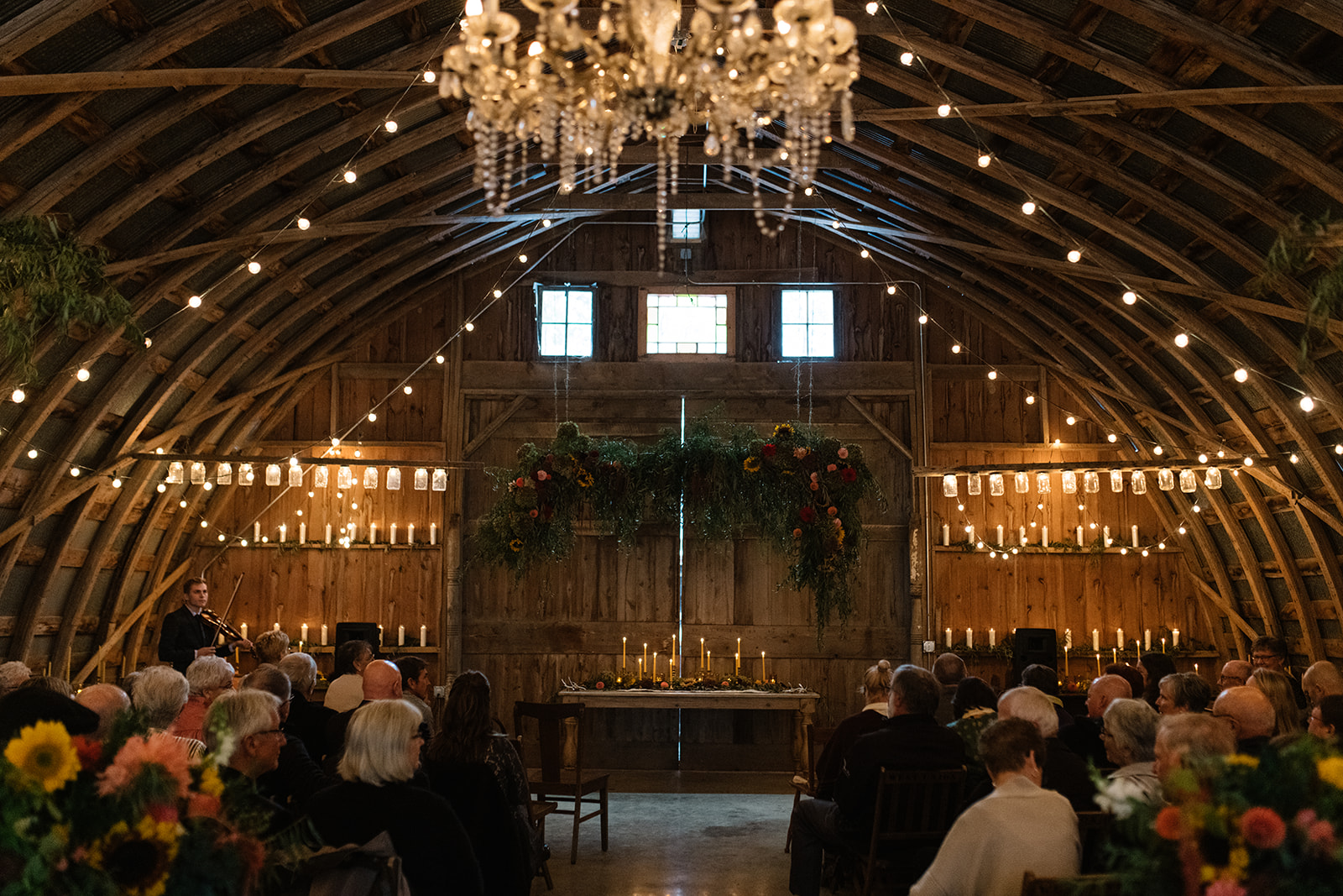 Wedding Ceremony with string lights at The Barn Wellman Iowa Wedding Venue inside