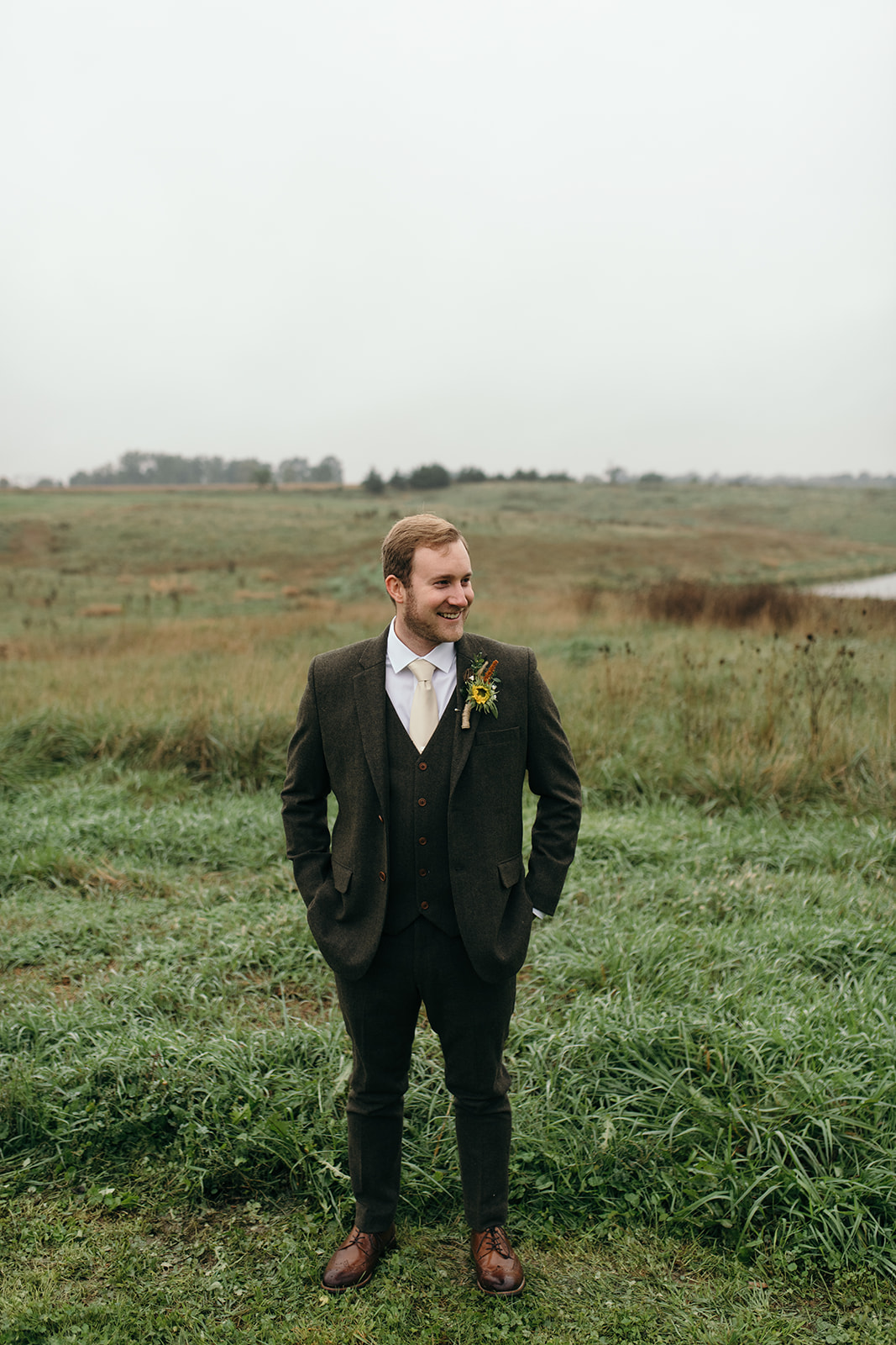 groom standing in field tweed suit iowa fall wedding