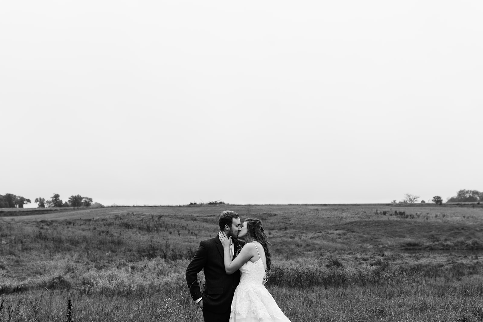 bride and groom kissing in field wellman iowa wedding