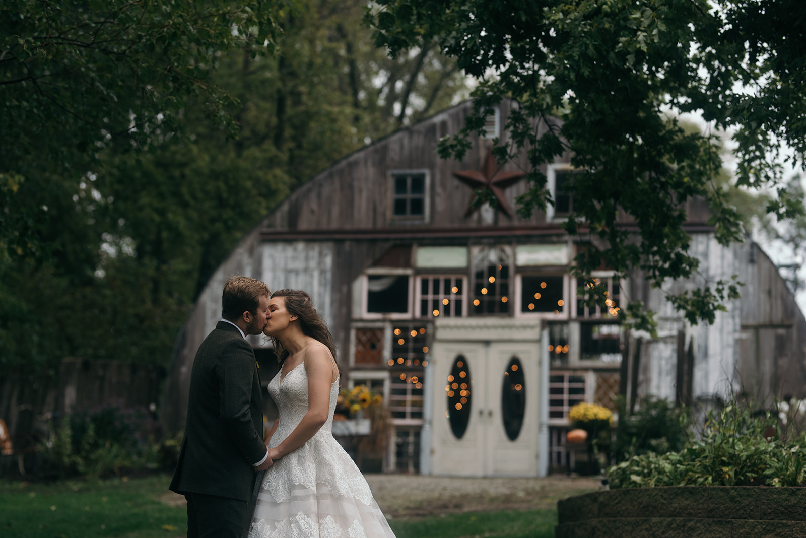 bride and groom kissing outside the barn wedding venue