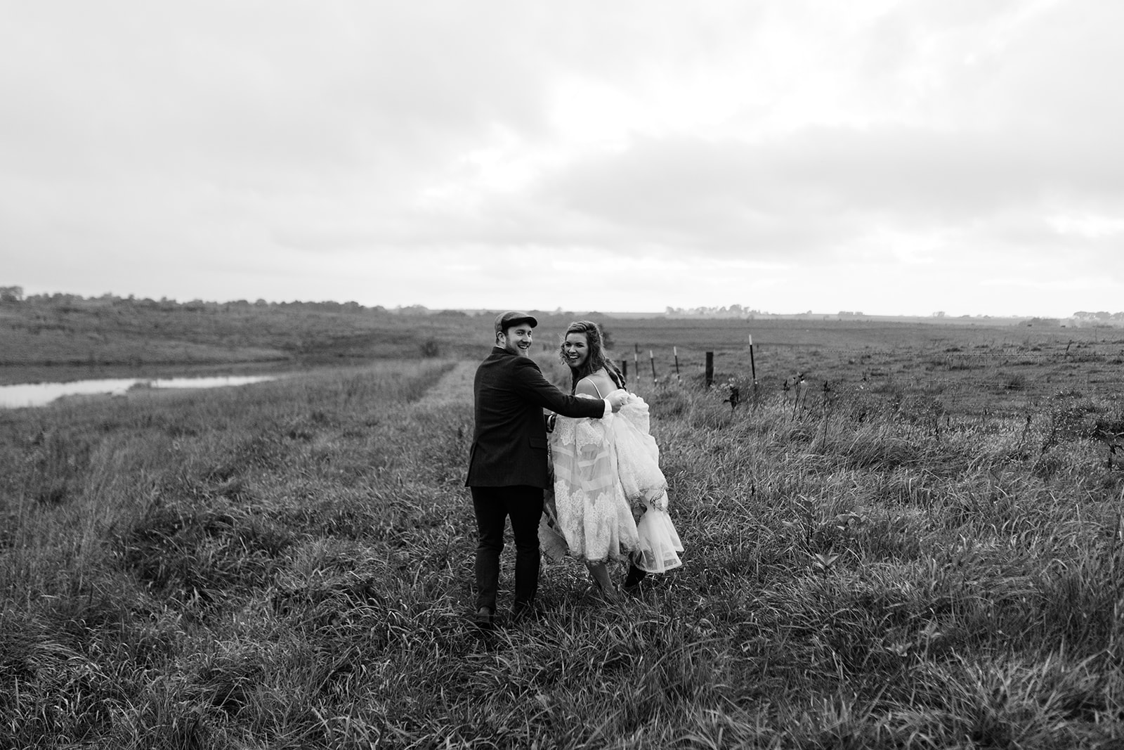 bride and groom running in field iowa fall wedding