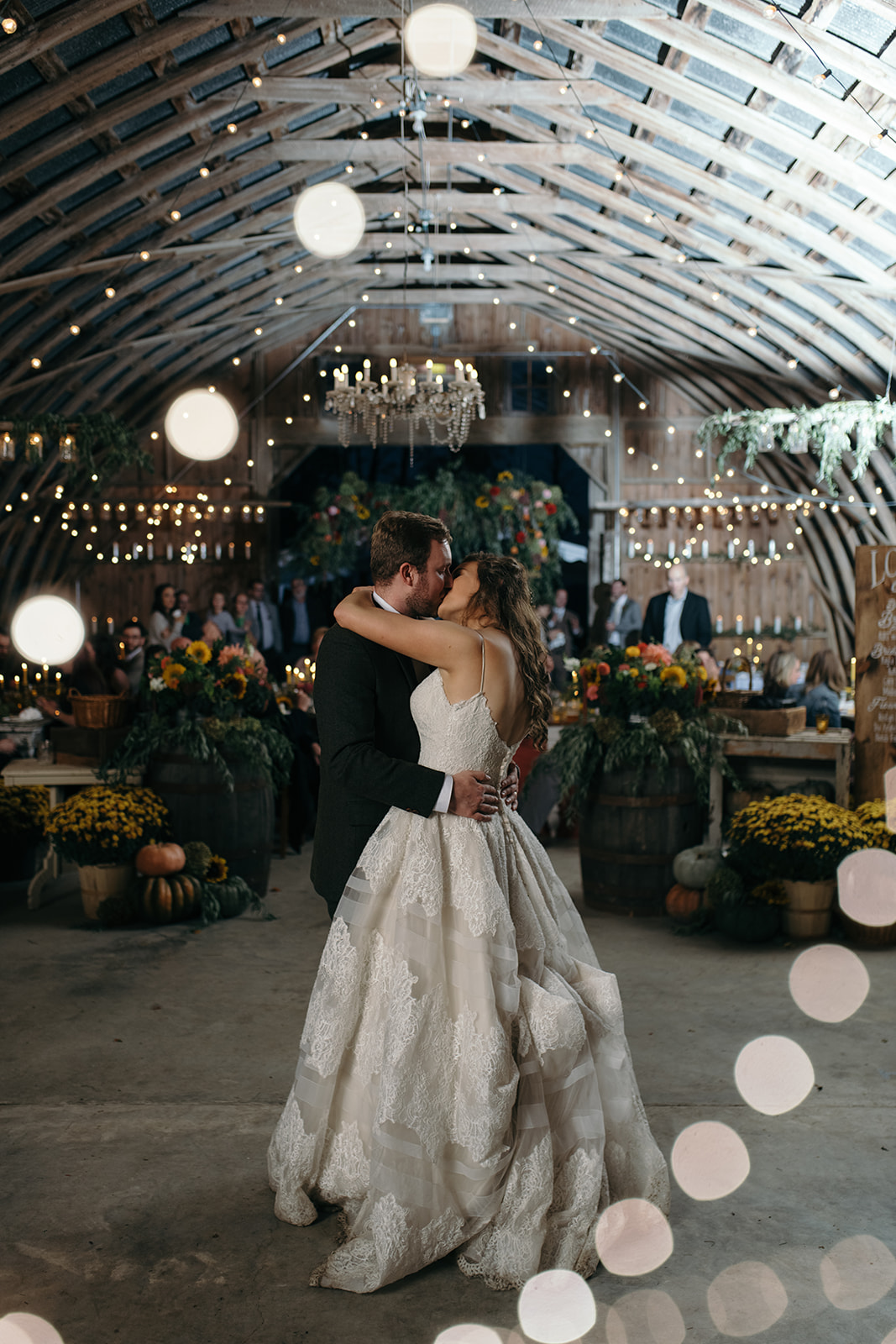 Bride and groom first dance at the barn wellman iowa wedding venue under string lights