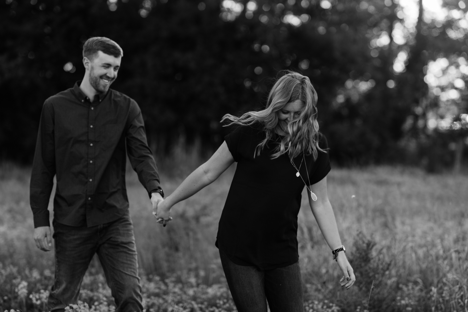 couple walking in field george wyth state park engagement