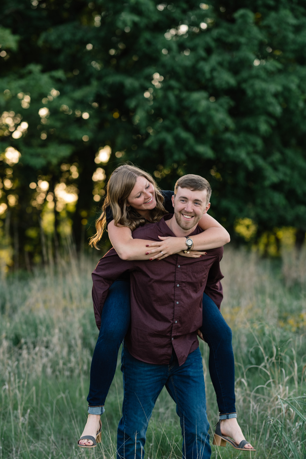 couple piggy back ride in field sunset george wyth state park engagement session