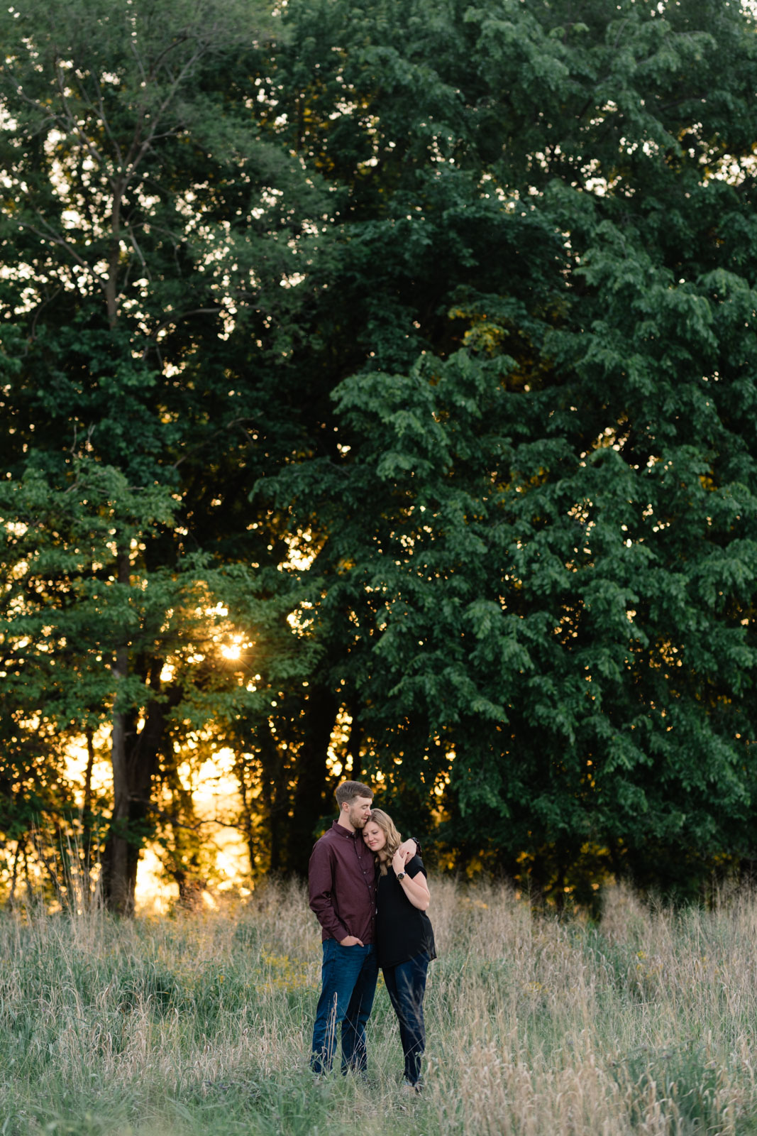 couple in field sunset george wyth state park engagement session
