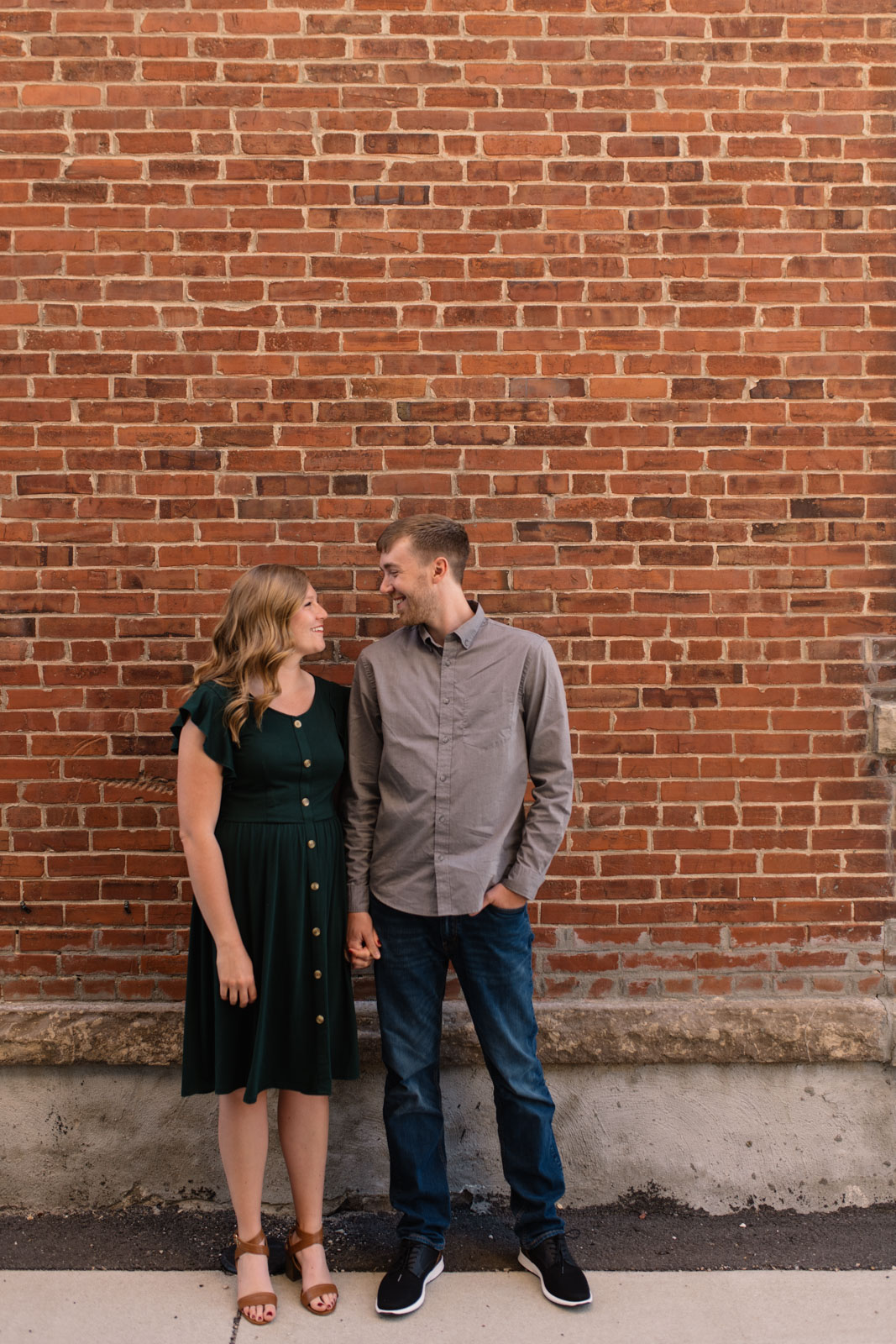 couple standing by brick wall cedar falls engagement