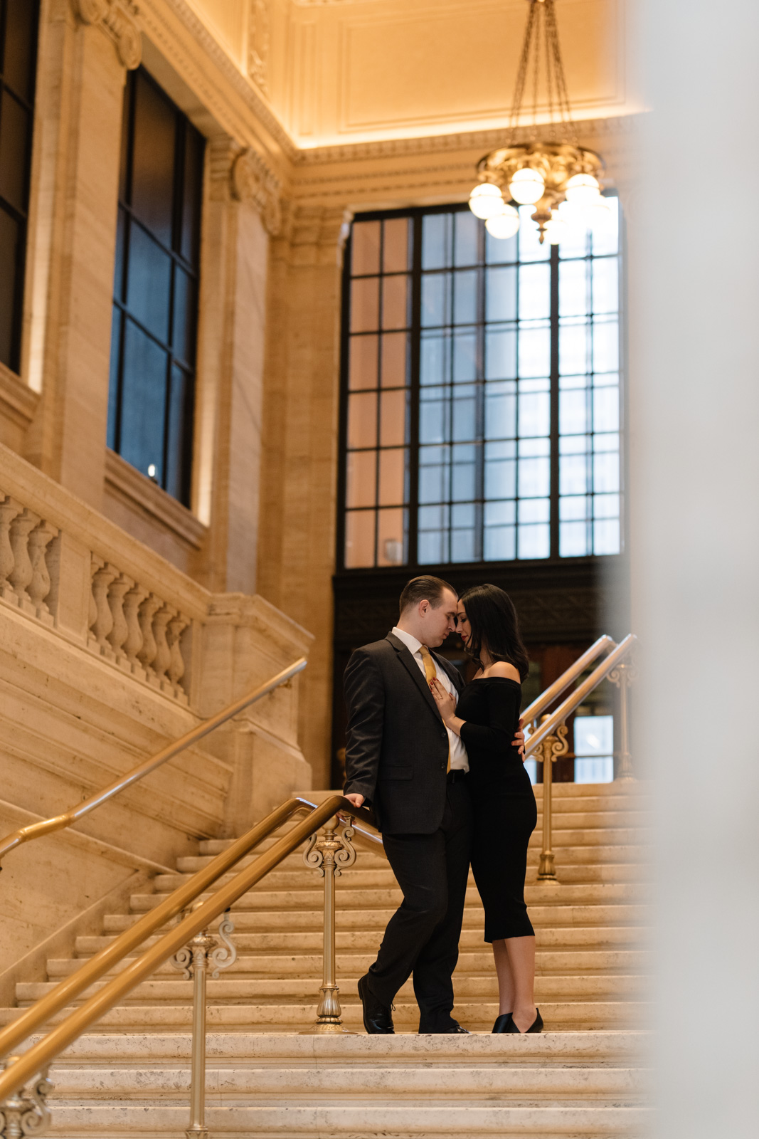 Couple cuddling on stairs at union station engagement