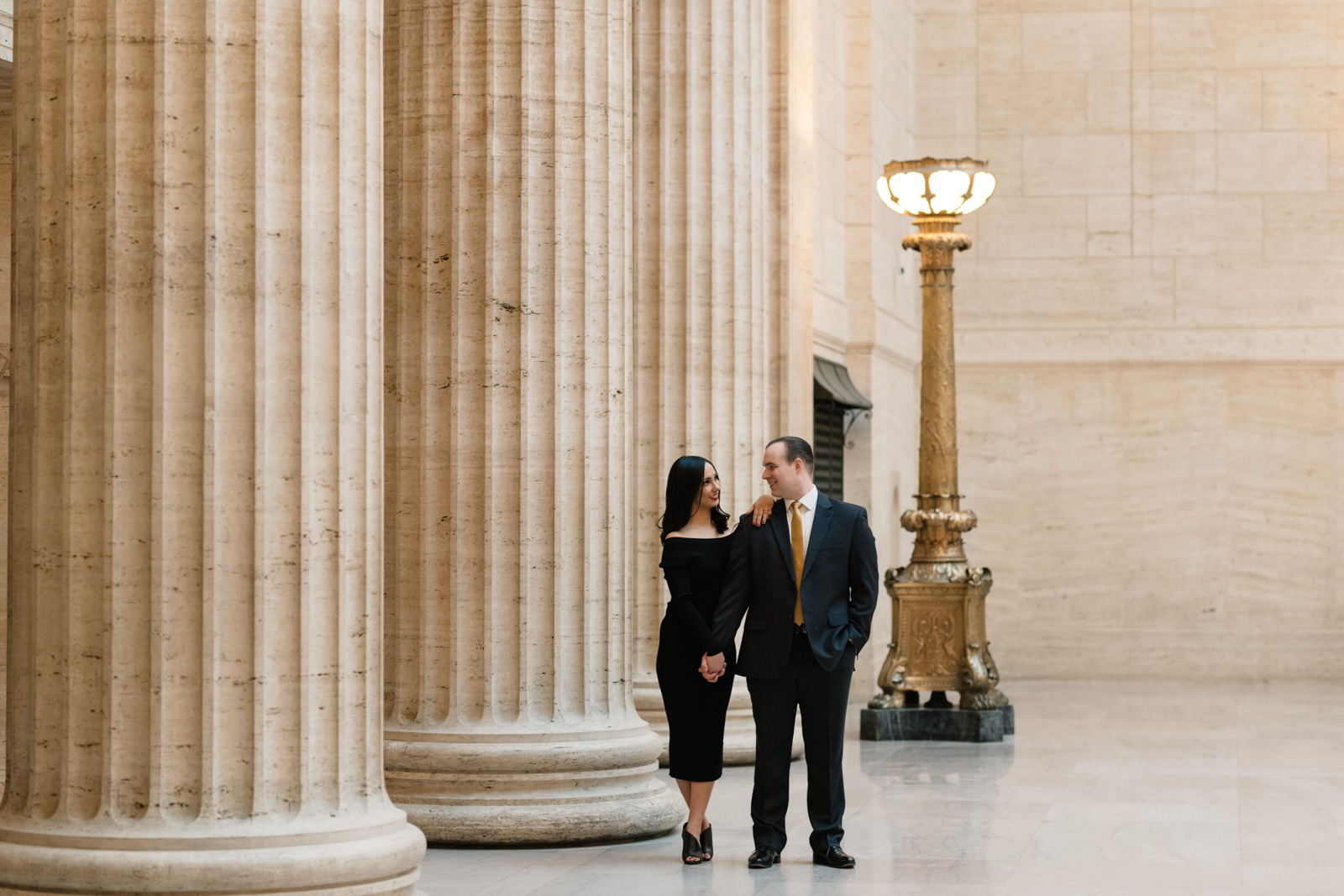 couple standing next to pillars at chicago union station engagement