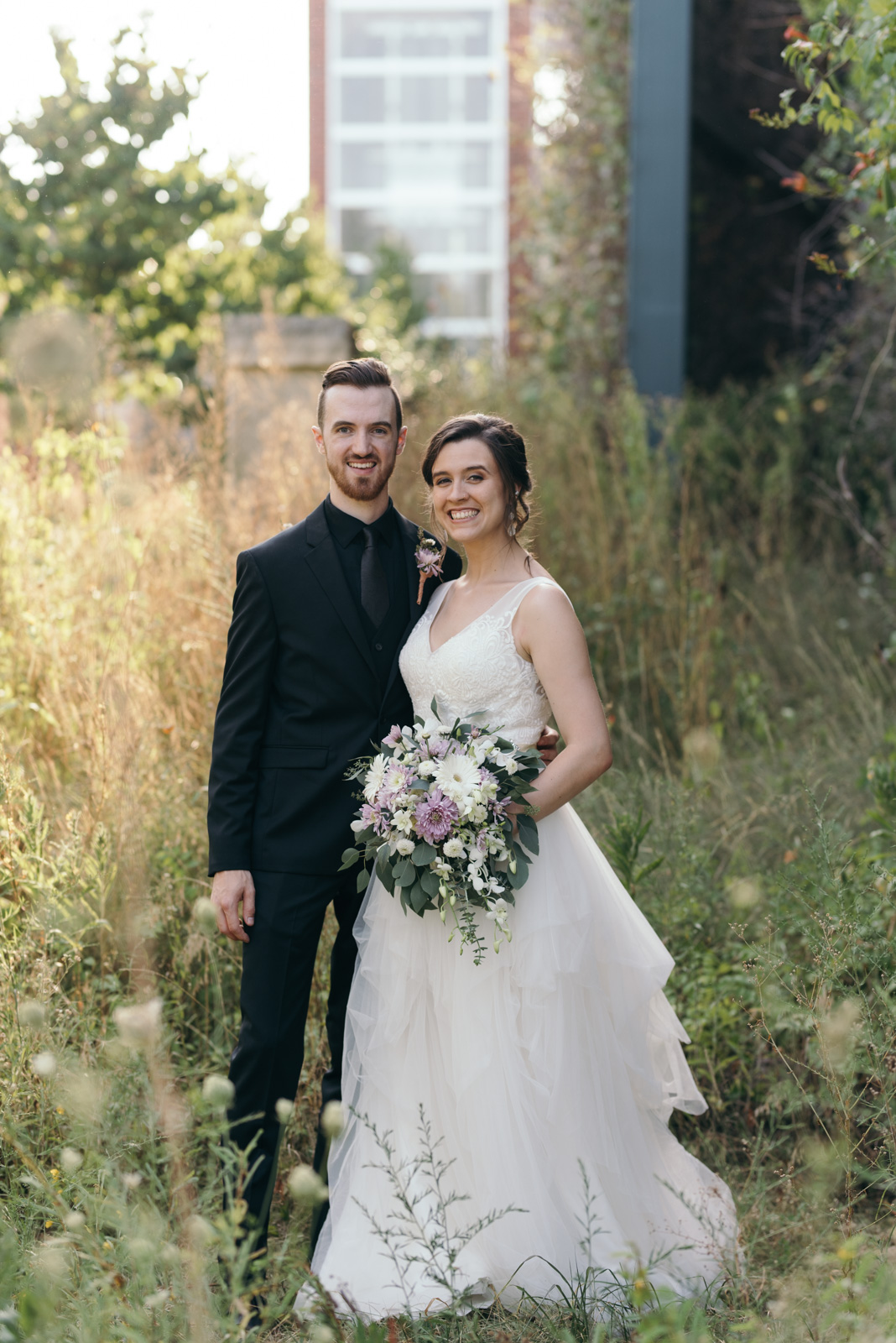 bride and groom smiling outside iowa city wedding