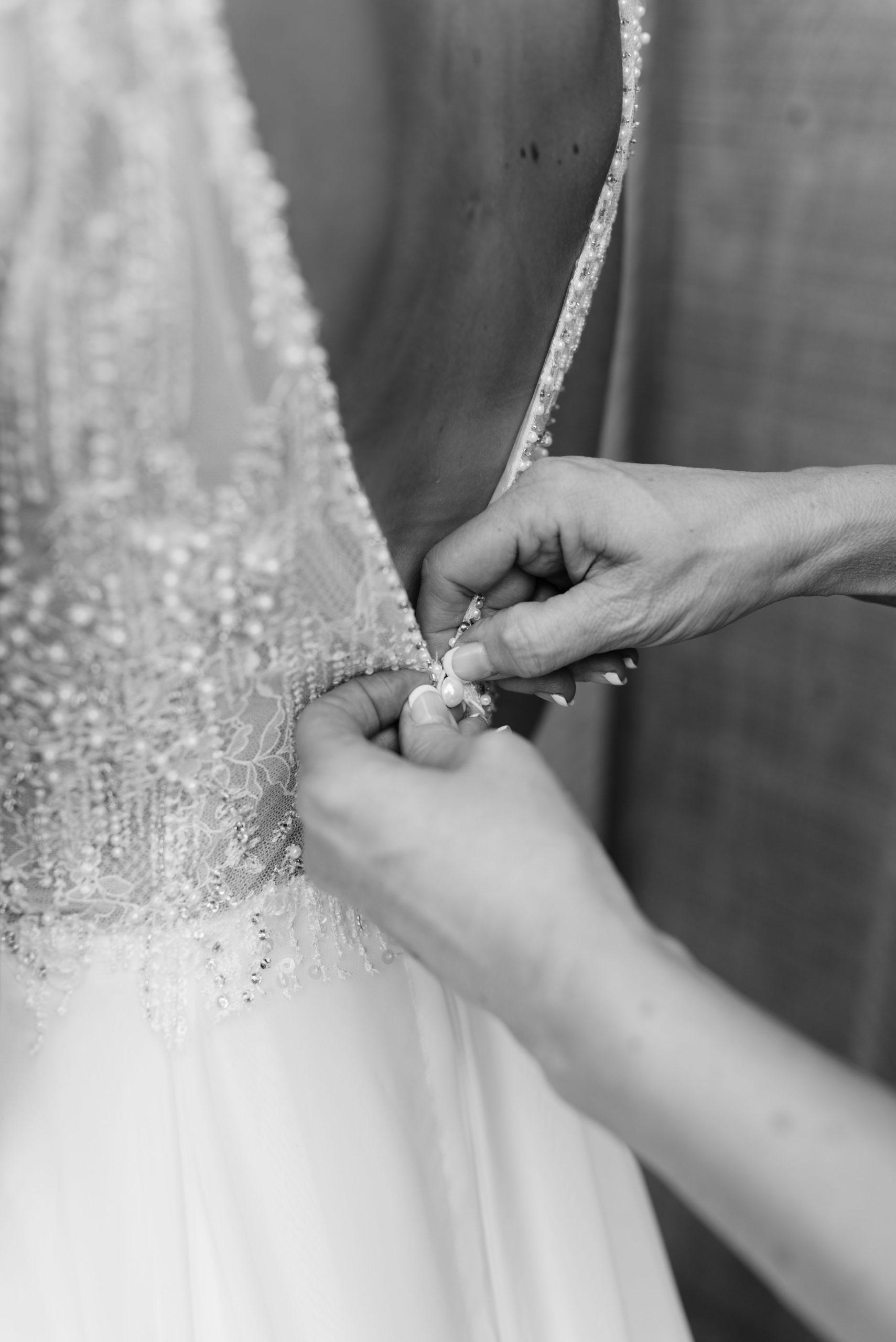 mom buttoning wedding dress schafer century barn wedding venue