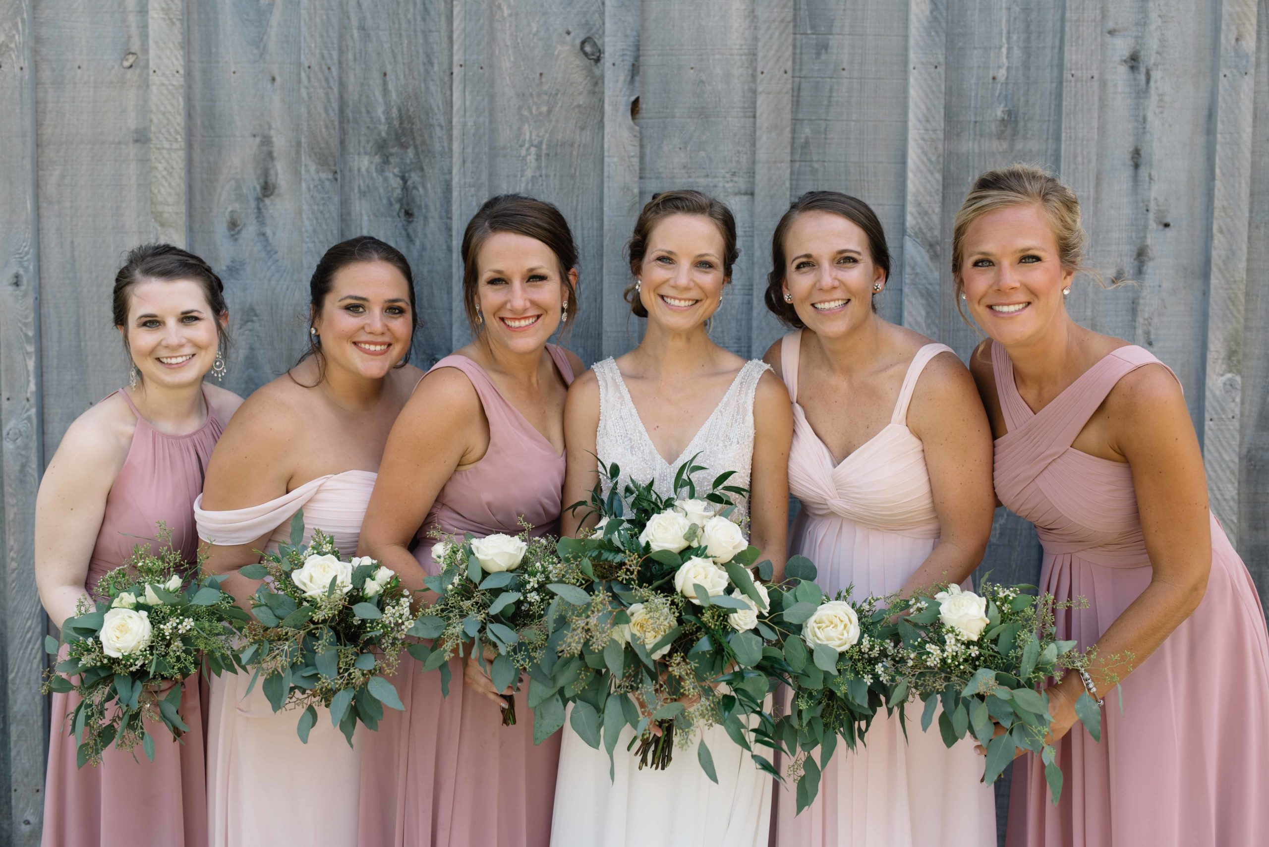 bridesmaid in blush pink dresses and gray wood barn schafer century barn wedding venue