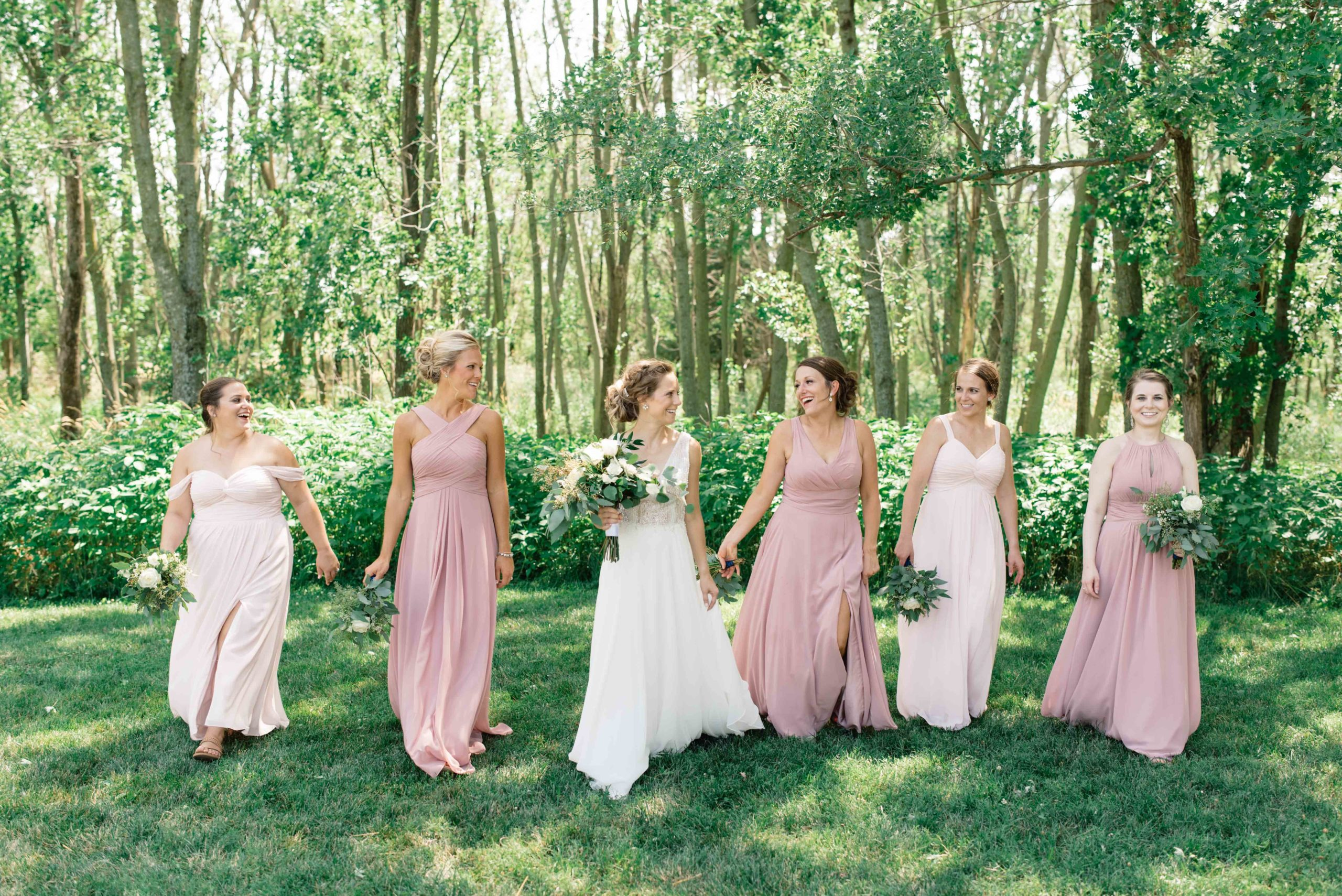 bridesmaid in blush pink dresses walking in forest schafer century barn wedding venue