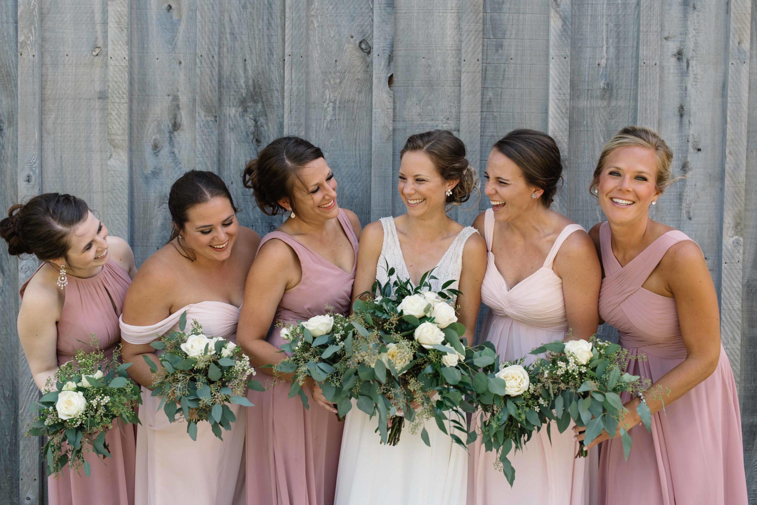 bridesmaids in blush pink dresses laughing with bride gray wood barn schafer century wedding venue