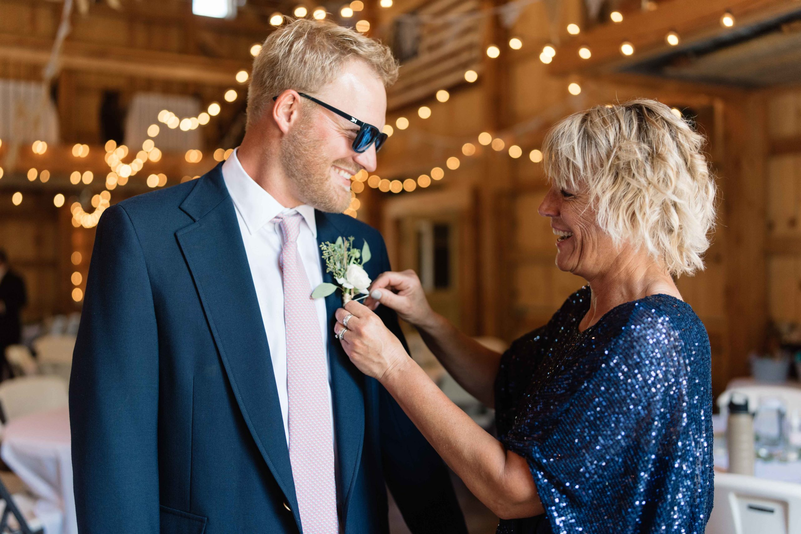 mom putting on grooms boutonniere with edison bulb lights schafer century barn Iowa wedding venue