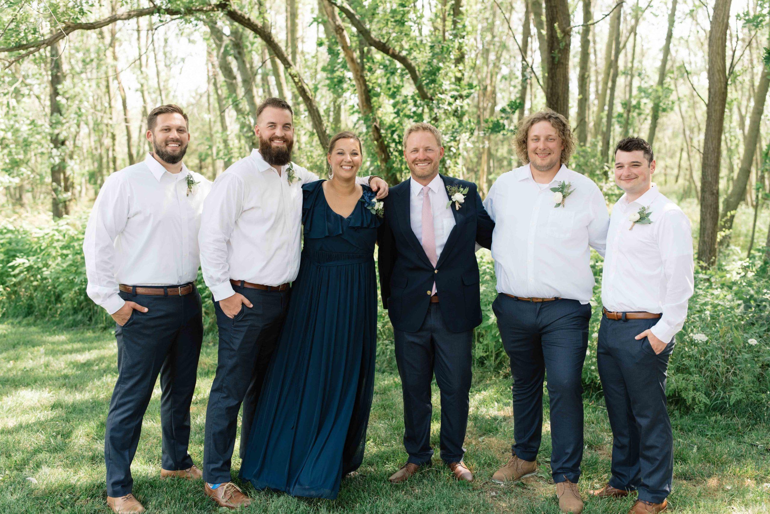groomsmen laughing with groom schafer century barn Iowa wedding venue