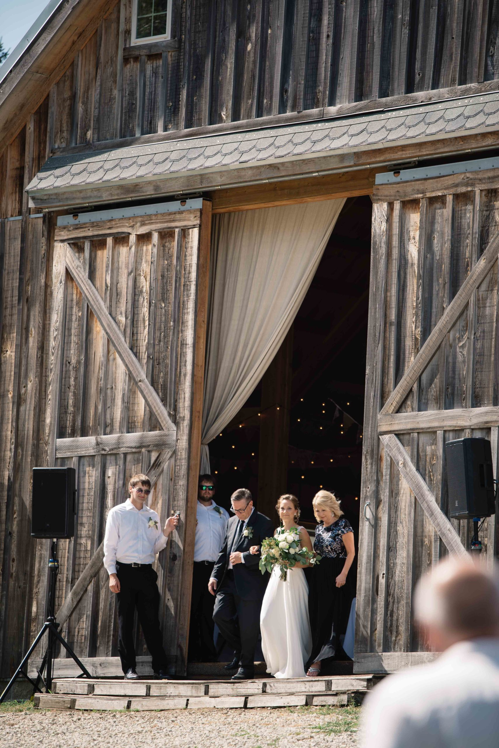 barn doors opening to reveal bride for outdoor Iowa barn wedding ceremony