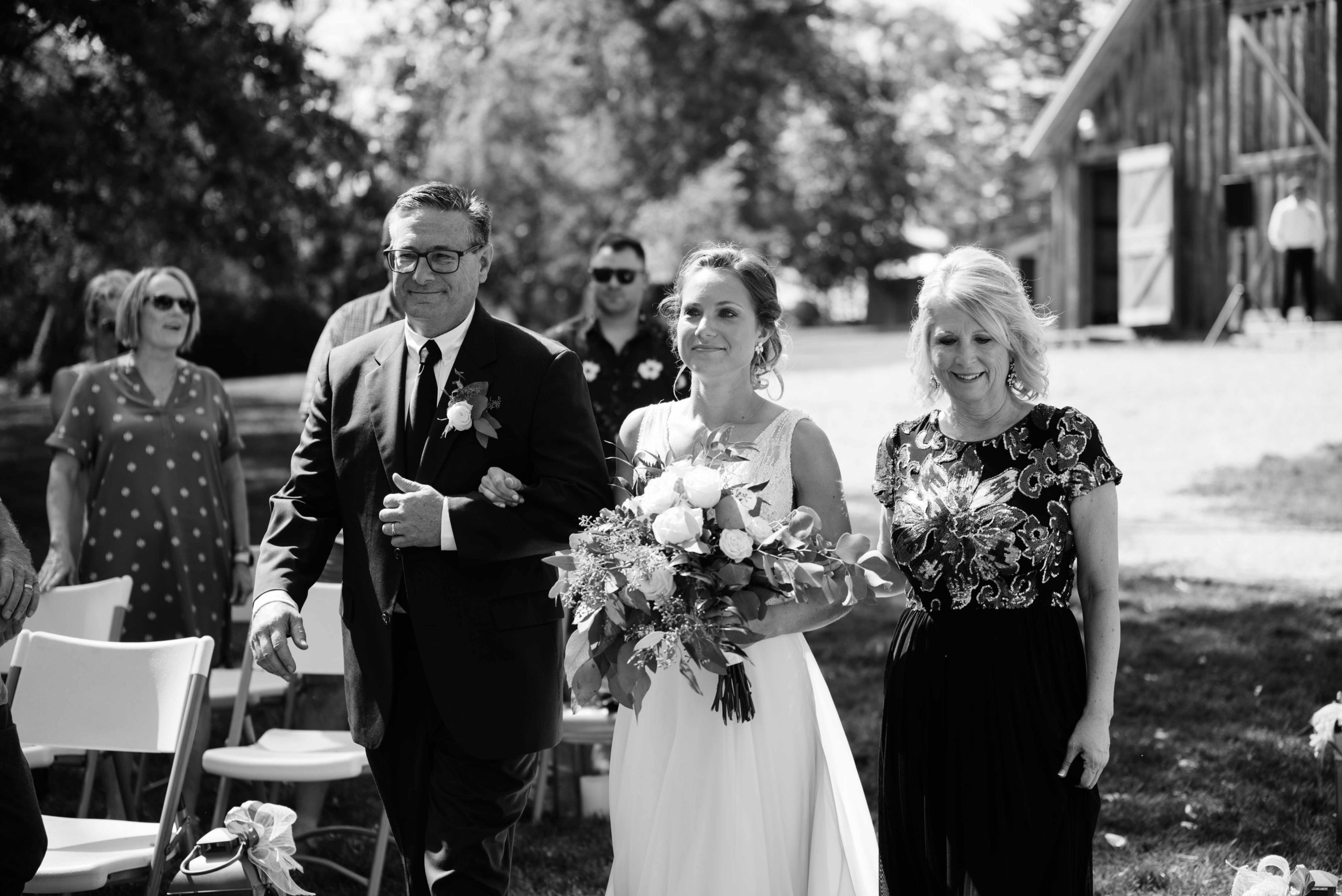 brides parents walking her down the aisle outdoor Iowa wedding ceremony schafer century barn