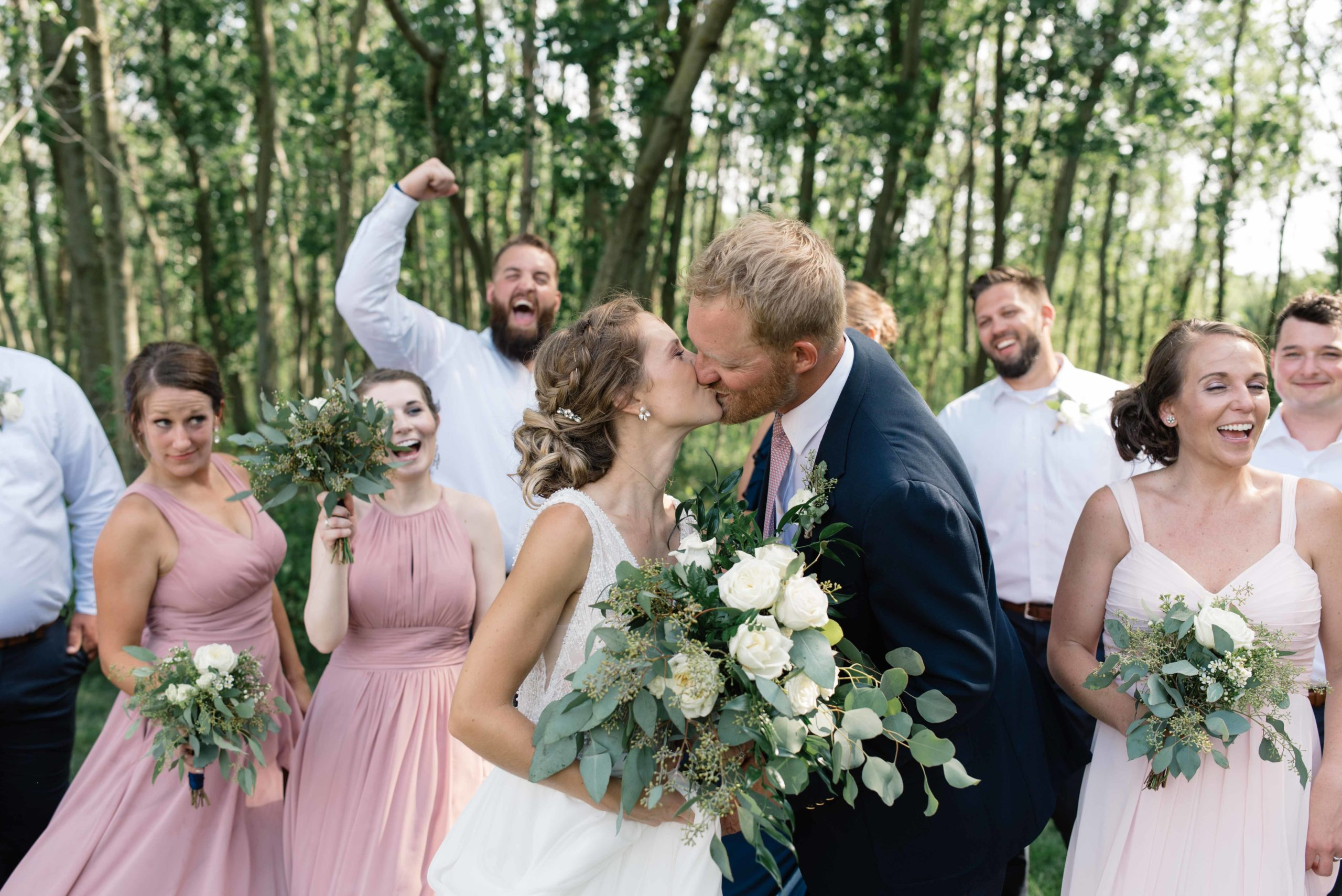 bridal party cheering as bride and groom kiss schafer century barn iowa wedding venue