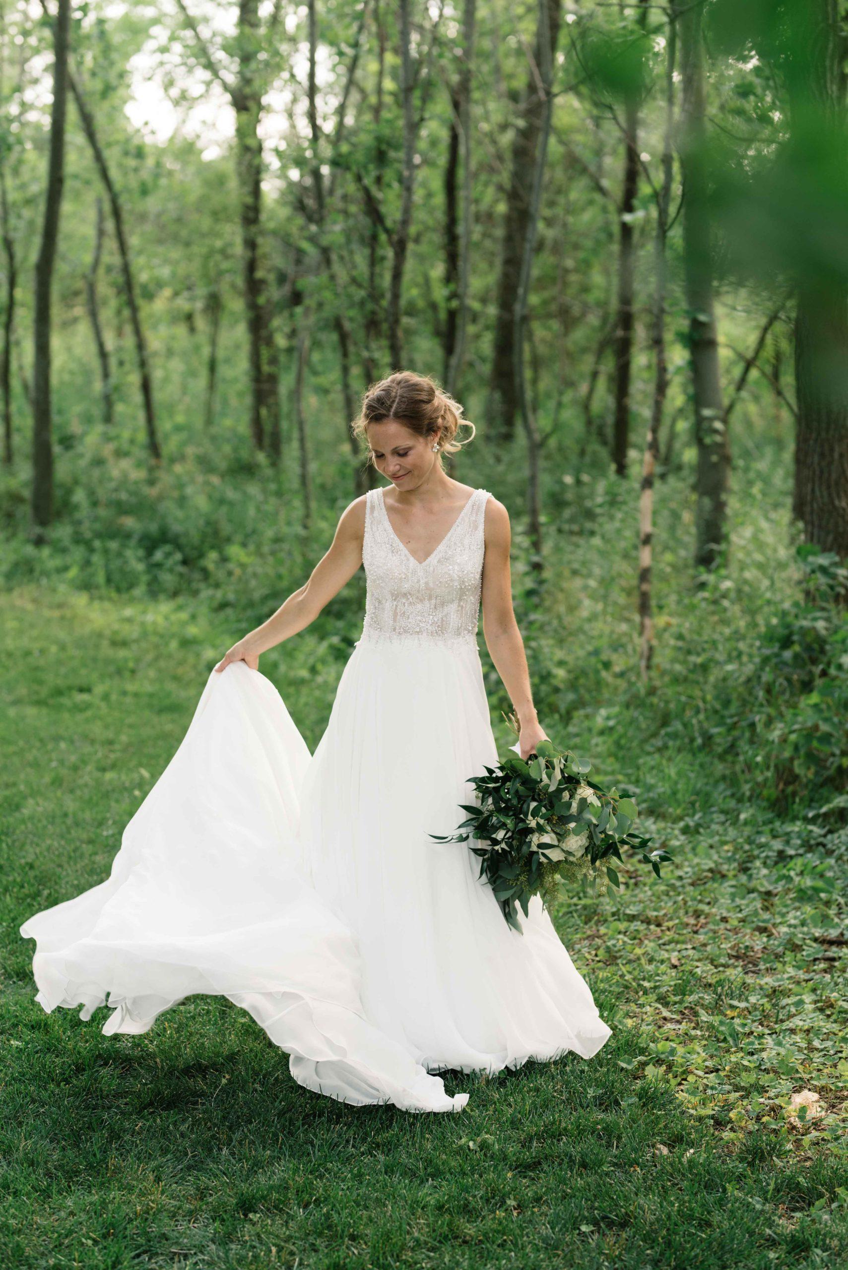 bride twirls in wedding dress under green trees schafer century barn wedding venue