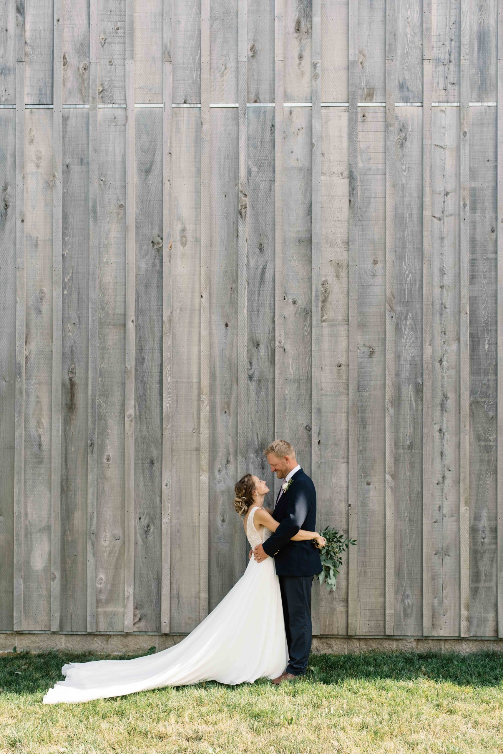 bride and groom in front of gray barn schafer century barn wedding venue