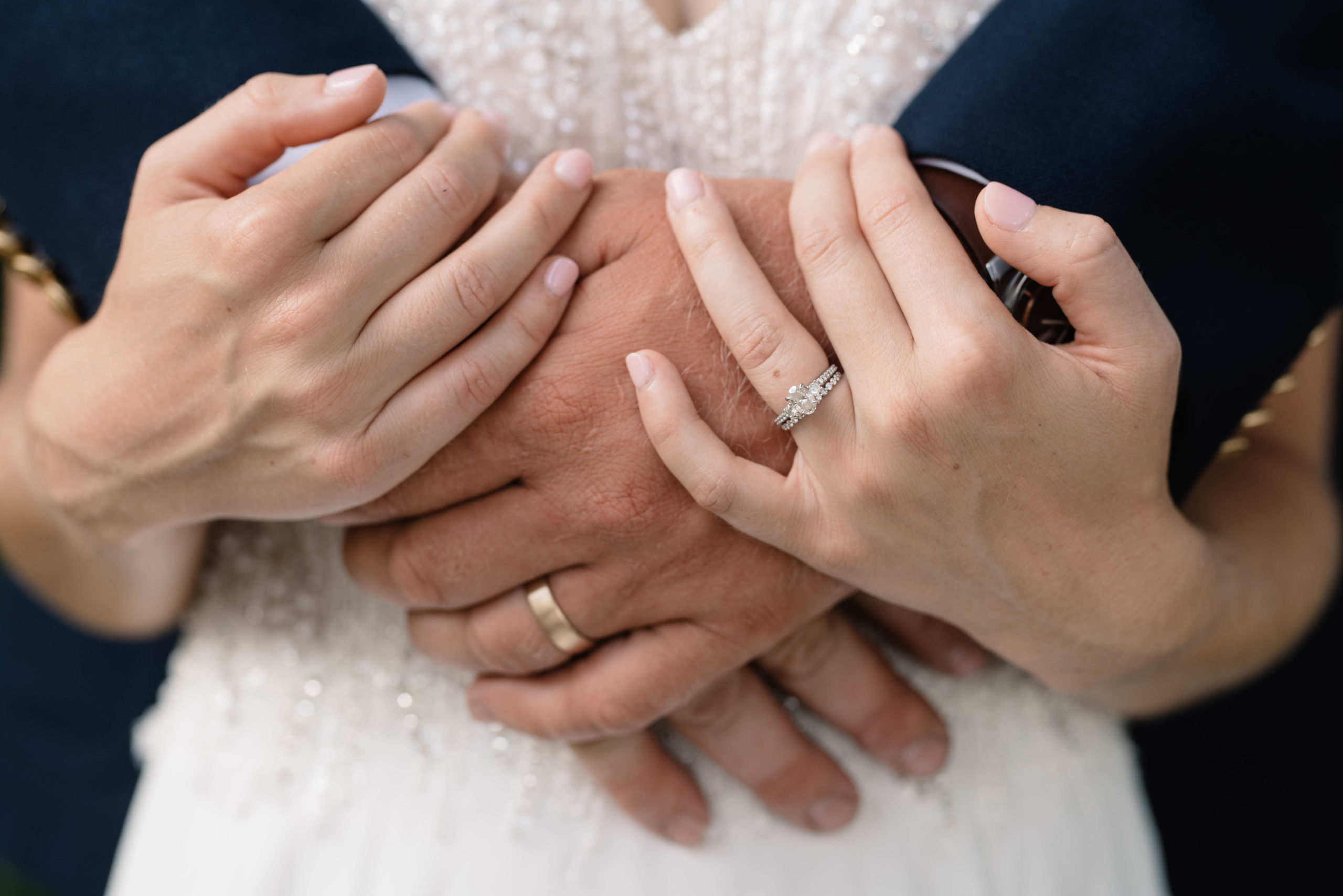 close up of bride and groom hands with wedding rings schafer century barn wedding venue