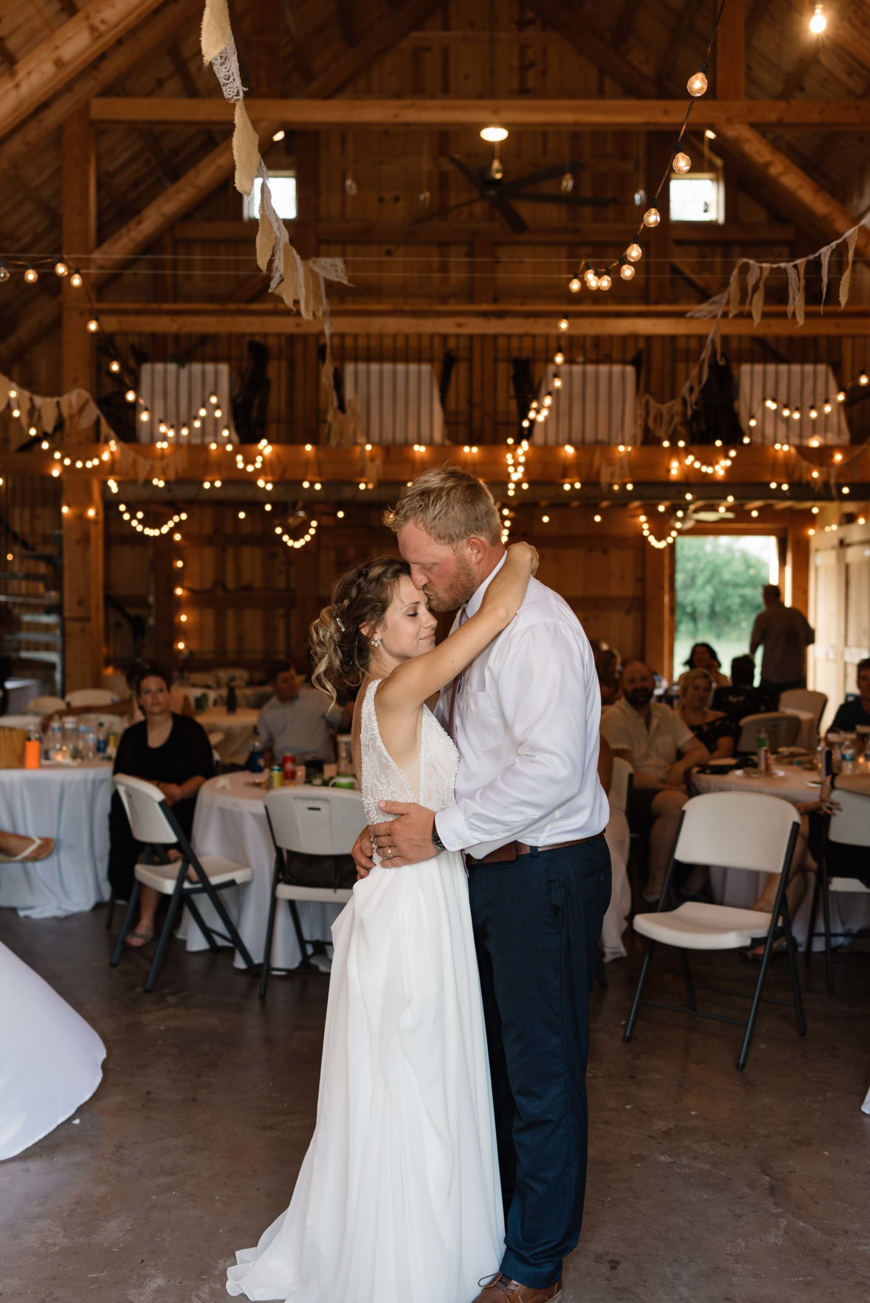 bride and groom first dance under twinkly edison bulb lights schafer century barn wedding venue