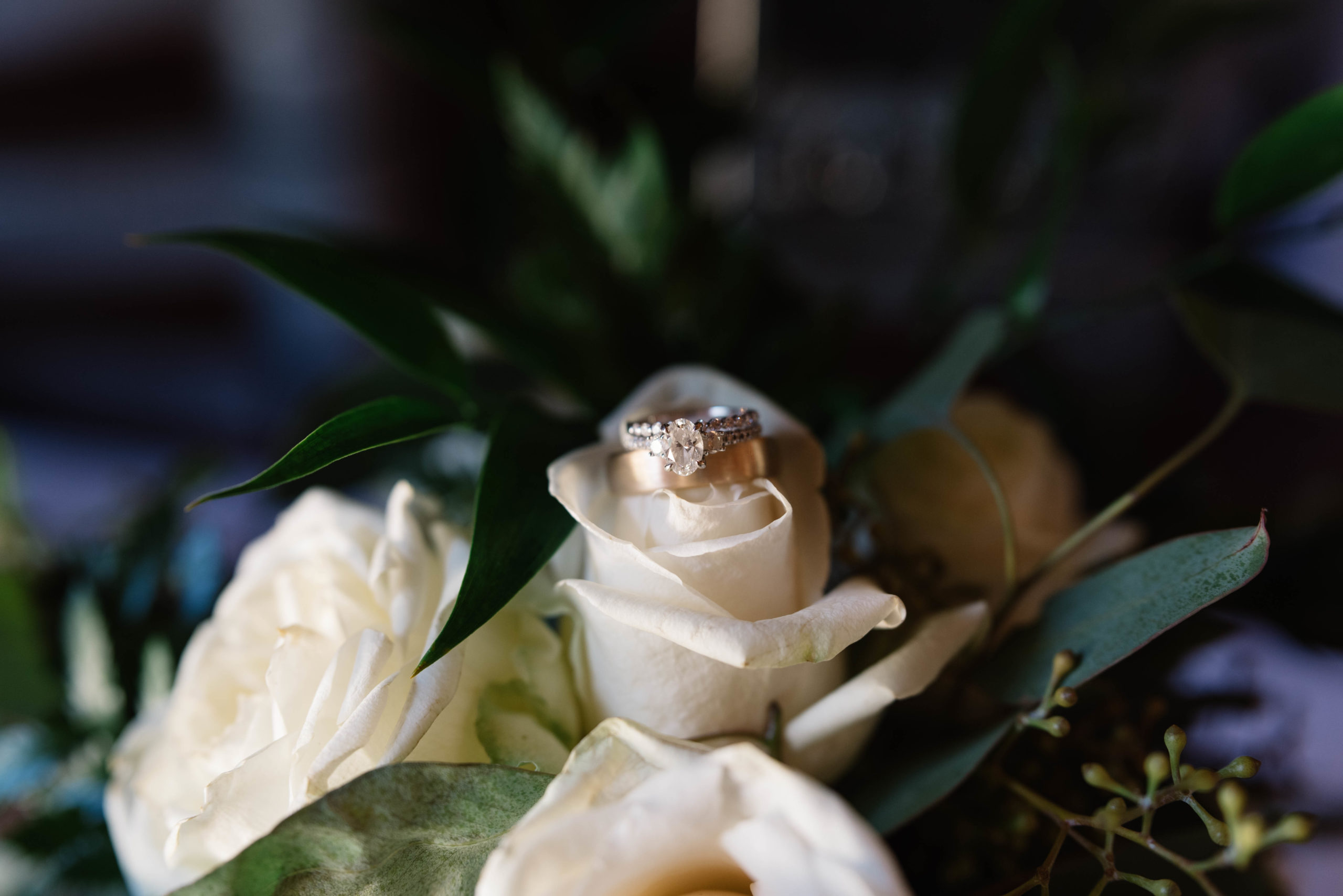 wedding rings on white rose wedding bouquet