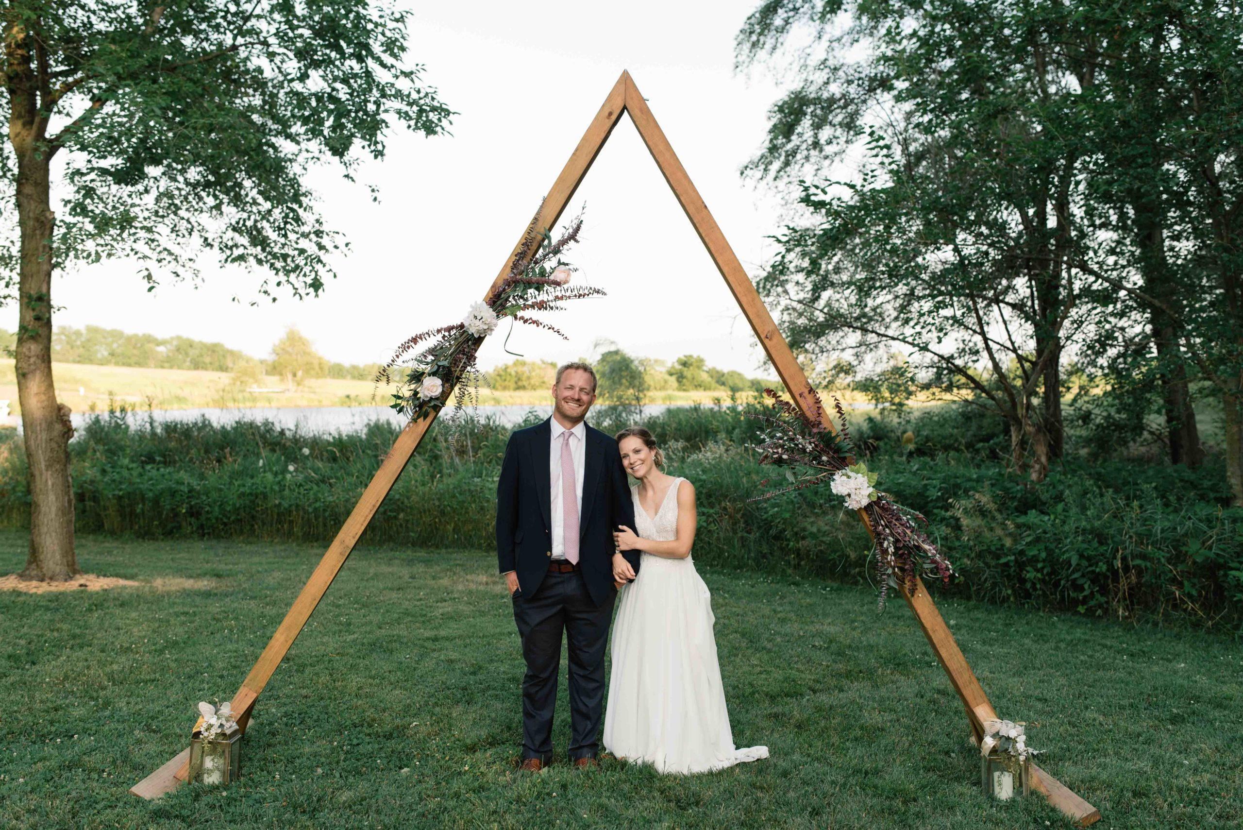 bride and groom snuggle under wooden triangle wedding ceremony arch schafer century barn wedding venue