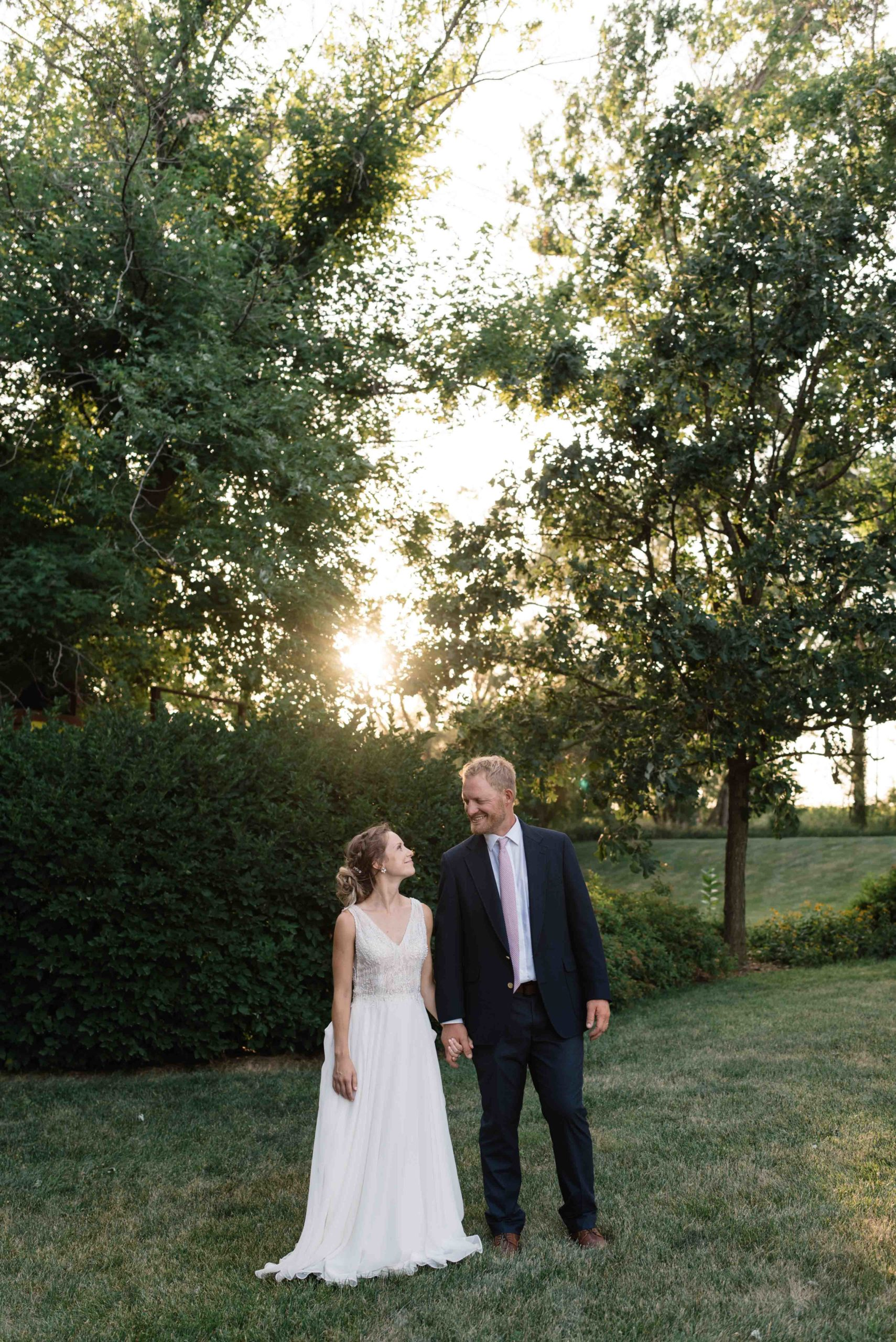 bride and groom holding hands at sunset outside schafer century barn wedding venue