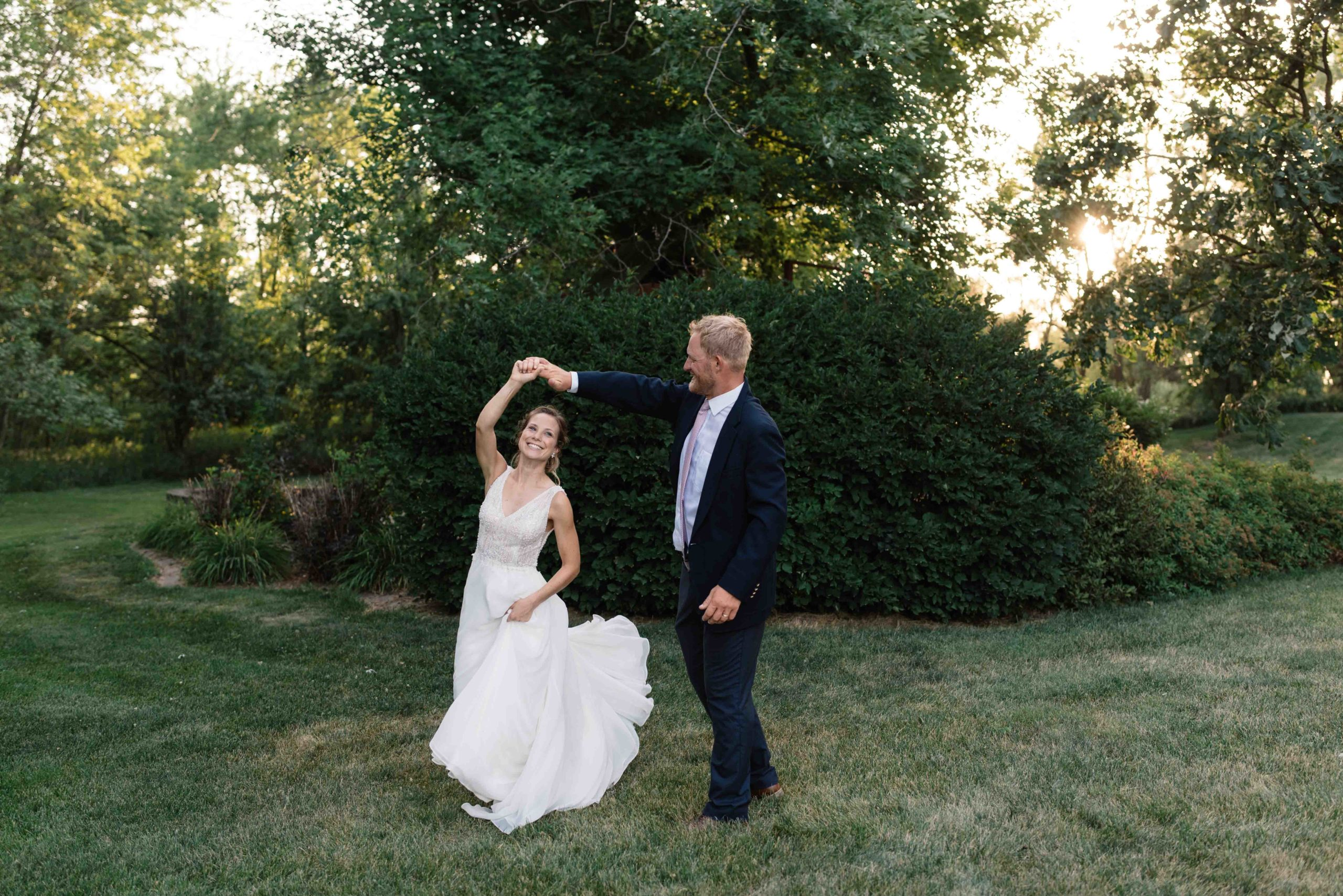 bride and groom twirling at sunset outside of schafer century barn wedding venue