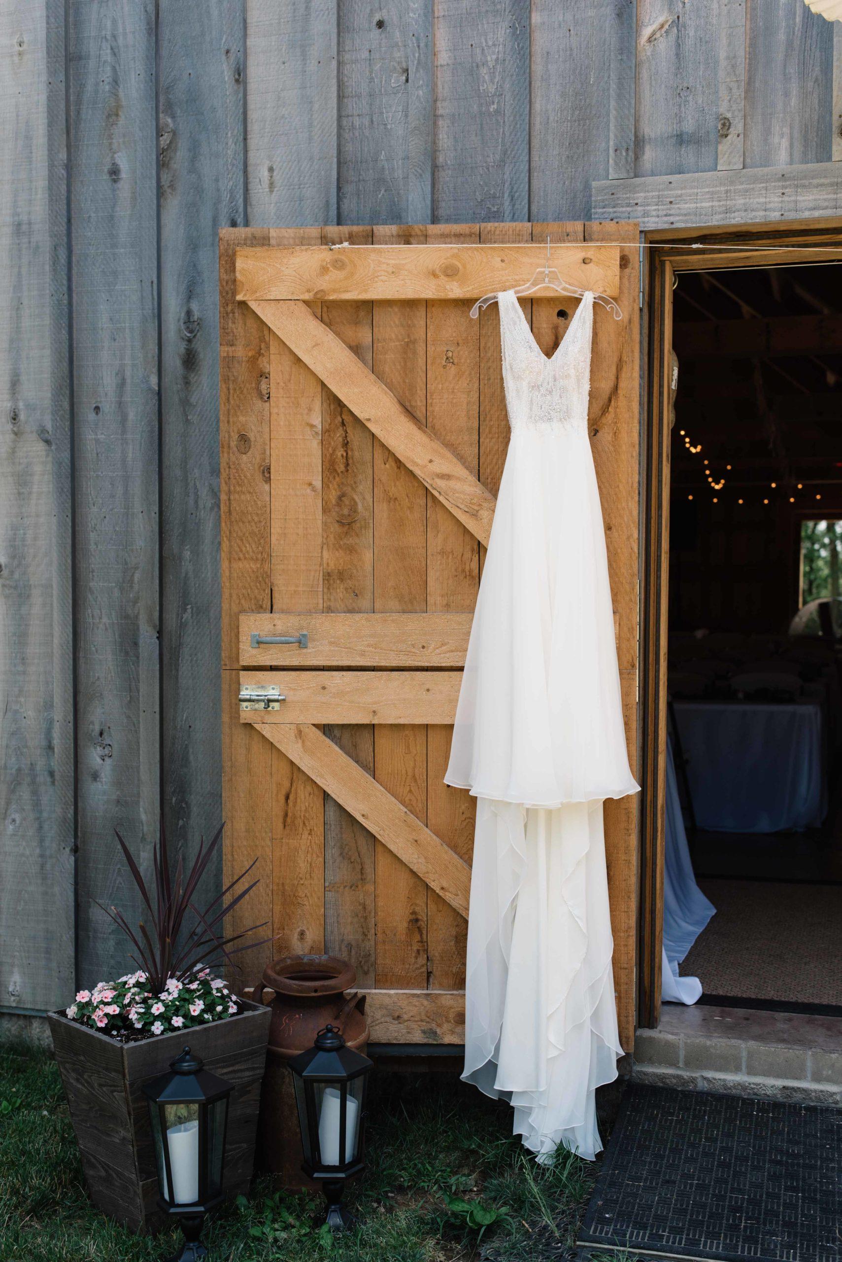 wedding dress hanging on barn door schafer century barn wedding venue